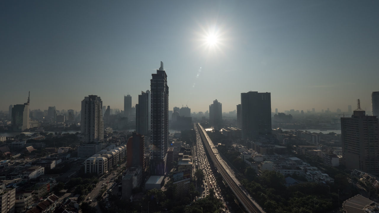 Cityscape of Bangkok, Thailand. Bright morning sun shining over the metropolis with high-rise buildings and traffic on motorway Architecture ASIA Bangkok Building Car City Cityscape Cityscapes Flare Horizontal Illuminated Modern Morning Panorama Shine Sunlight Thailand Transportation Travel Destinations Urban Skyline View