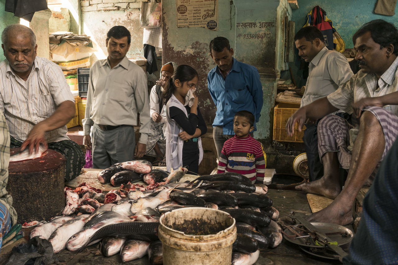 real people, men, market, food and drink, market stall, small business, retail, buying, food, freshness, large group of people, standing, outdoors, day, women, butcher, adult, young adult, people, adults only