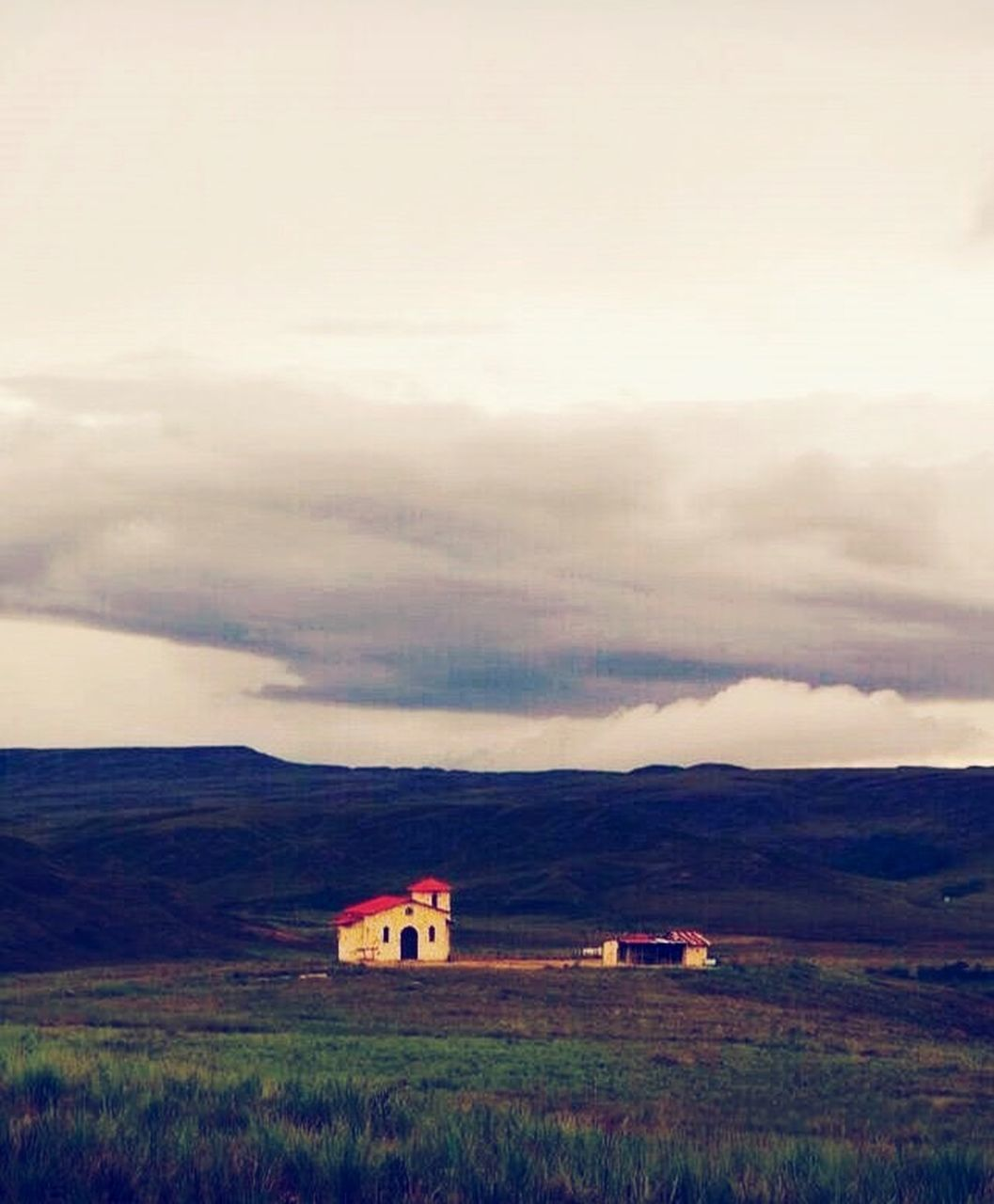 house, built structure, cloud - sky, building exterior, farmhouse, rural scene, landscape, field, outdoors, nature, architecture, residential building, grass, mountain, scenics, agriculture, no people, beauty in nature, day, storm cloud, sky