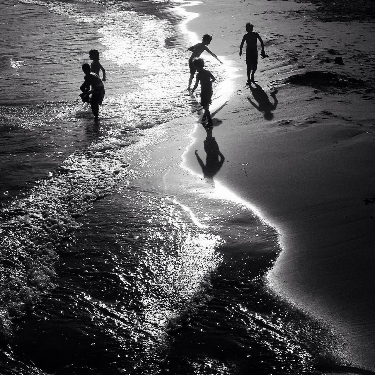 Silhouette Children Playing On Beach