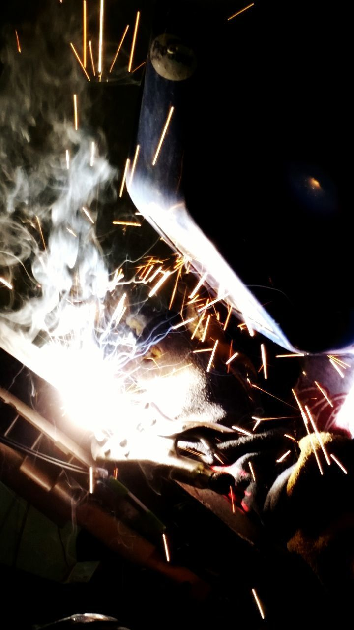 fire - natural phenomenon, burning, flame, heat - temperature, glowing, night, illuminated, indoors, close-up, light - natural phenomenon, arts culture and entertainment, fire, low angle view, smoke - physical structure, bonfire, heat, firewood, lighting equipment, metal, sparks
