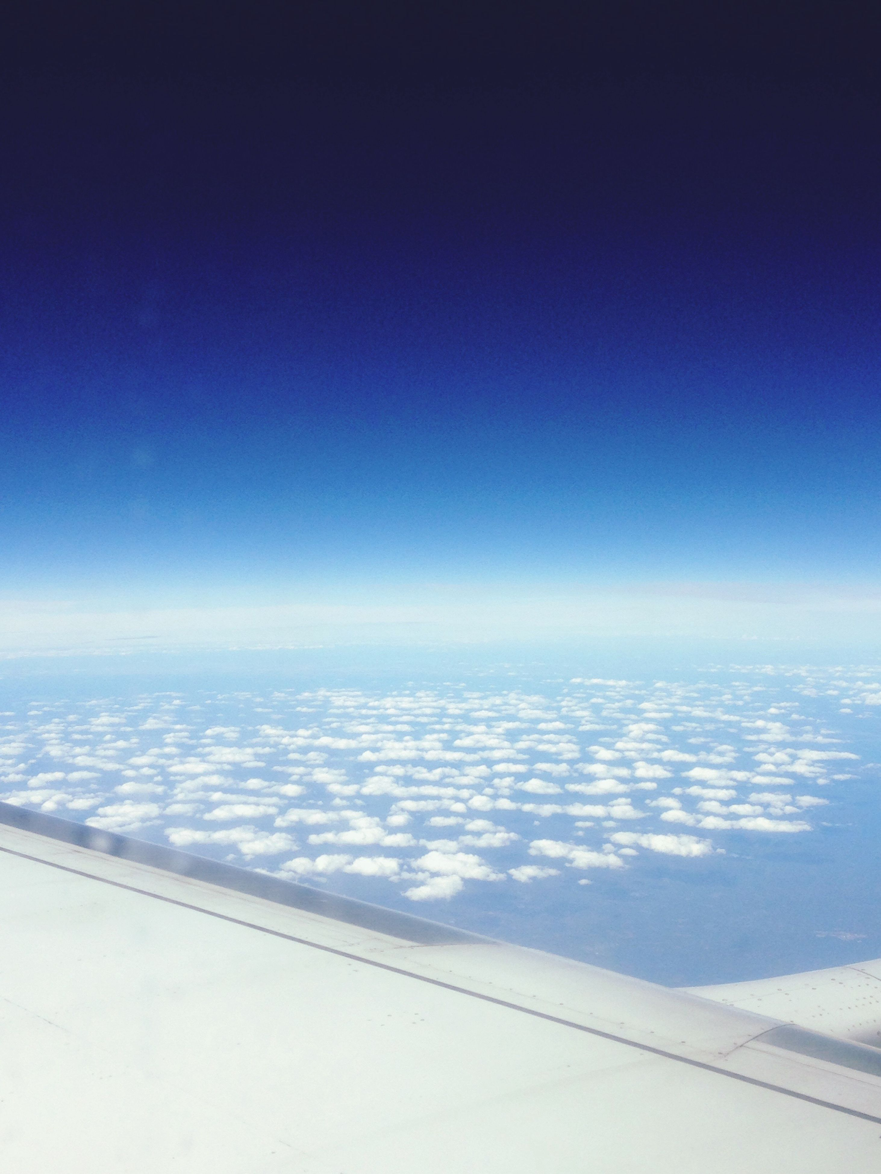 airplane, flying, blue, transportation, air vehicle, travel, cloudscape, scenics, mode of transport, on the move, part of, aircraft wing, aerial view, sky, cropped, clear sky, beauty in nature, white, copy space, majestic, cloud, cloud - sky, the natural world, tranquil scene, journey, nature, day, tranquility, meteorology, mid-air, heaven, sea