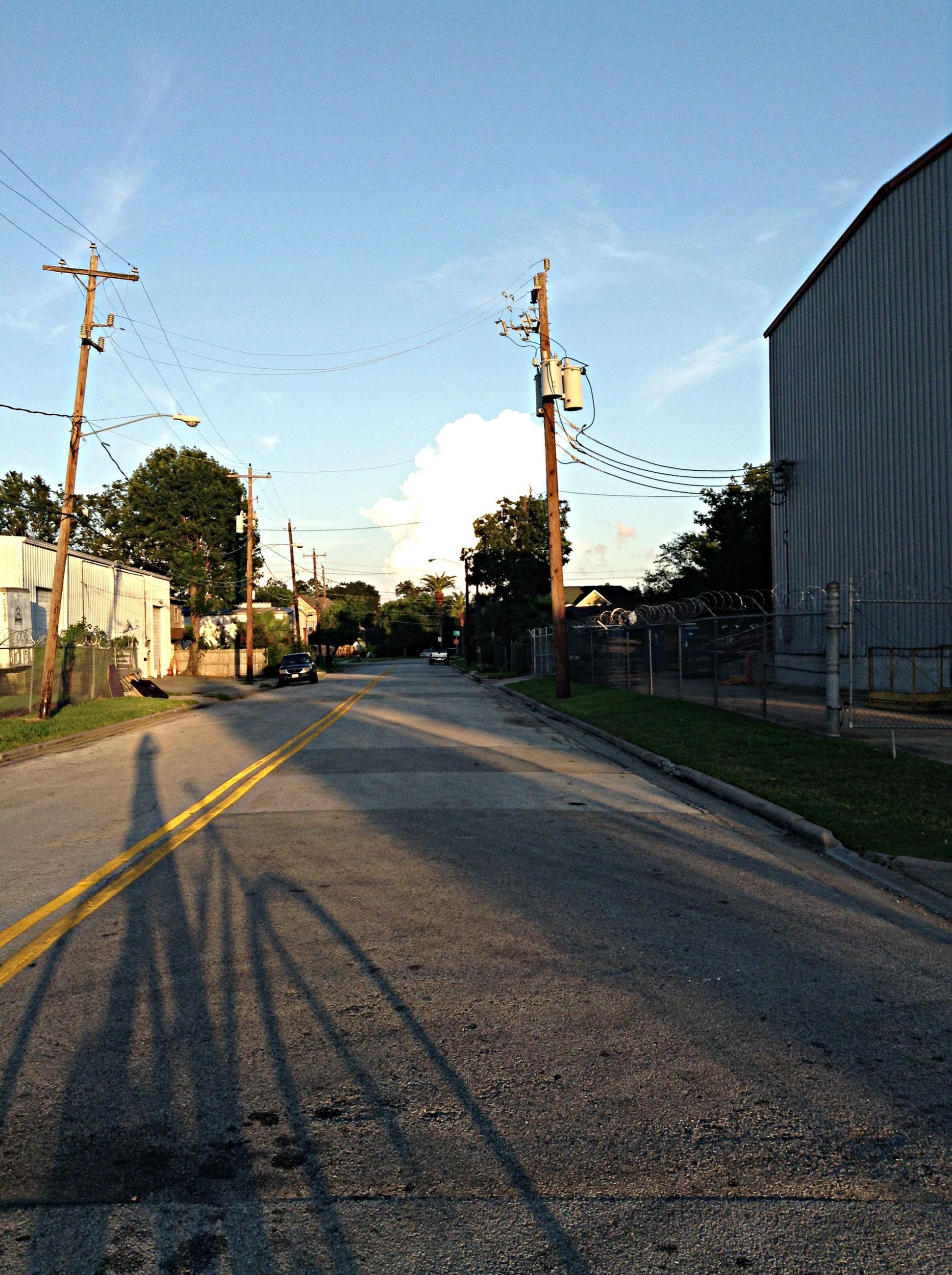 the way forward, building exterior, transportation, architecture, built structure, road, street, diminishing perspective, sky, vanishing point, street light, road marking, electricity pylon, power line, empty, empty road, city, asphalt, long, outdoors