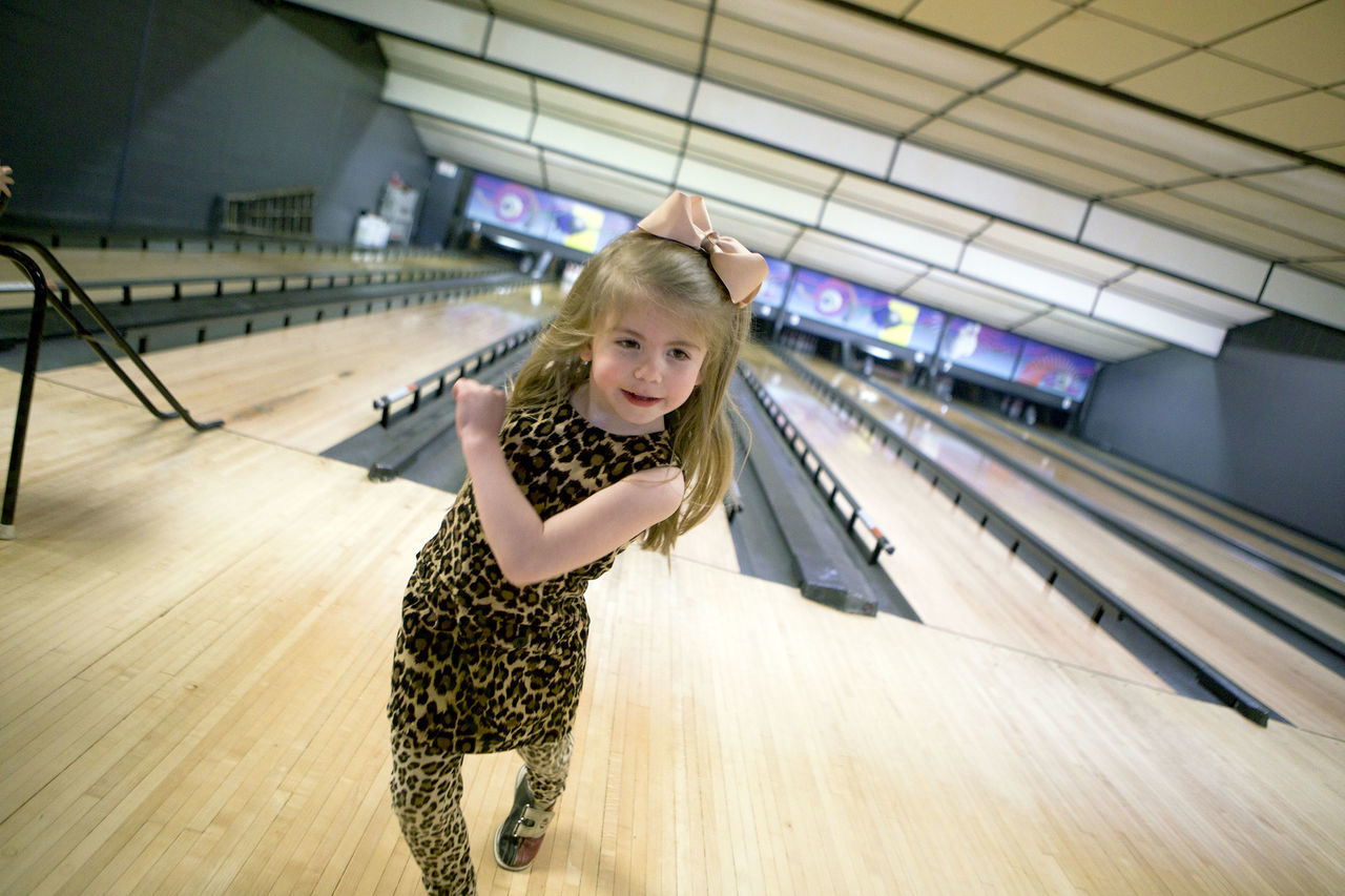 A five-year-old girl does a victory move after getting a strike while bowling. 5-year-old Beauty Bowling Bowling Alley Canon Childhood Fun Indoors  Leopard Print One Girl Only One Person Real People Smiling Sport Sports Sports Photography Victory Win Winner