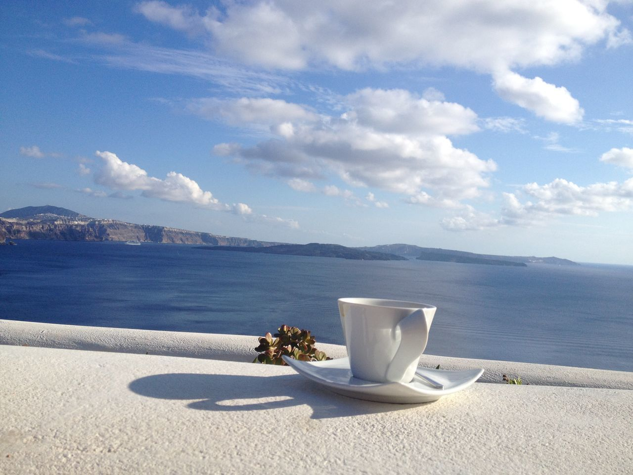 Coffee Cup By Sea Against Cloudy Sky