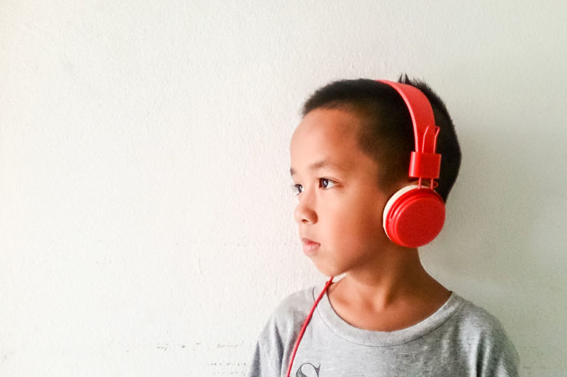 Boy With Headphones. Boy Check It Out Childhood Children Ear Everyday Emotion EyeEm Best Edits EyeEm Best Shots Headphones Human Face Leisure Leisure Activity Lifestyles Listening To Music Music Portrait Radio Relax Song Sound Of Life Voice White Background