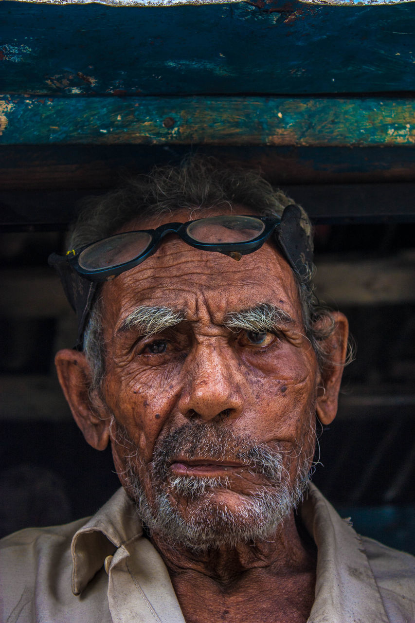 senior adult, senior men, real people, one person, eyeglasses, front view, one senior man only, lifestyles, focus on foreground, glasses, portrait, leisure activity, looking at camera, beard, headshot, human face, outdoors, day, close-up, people