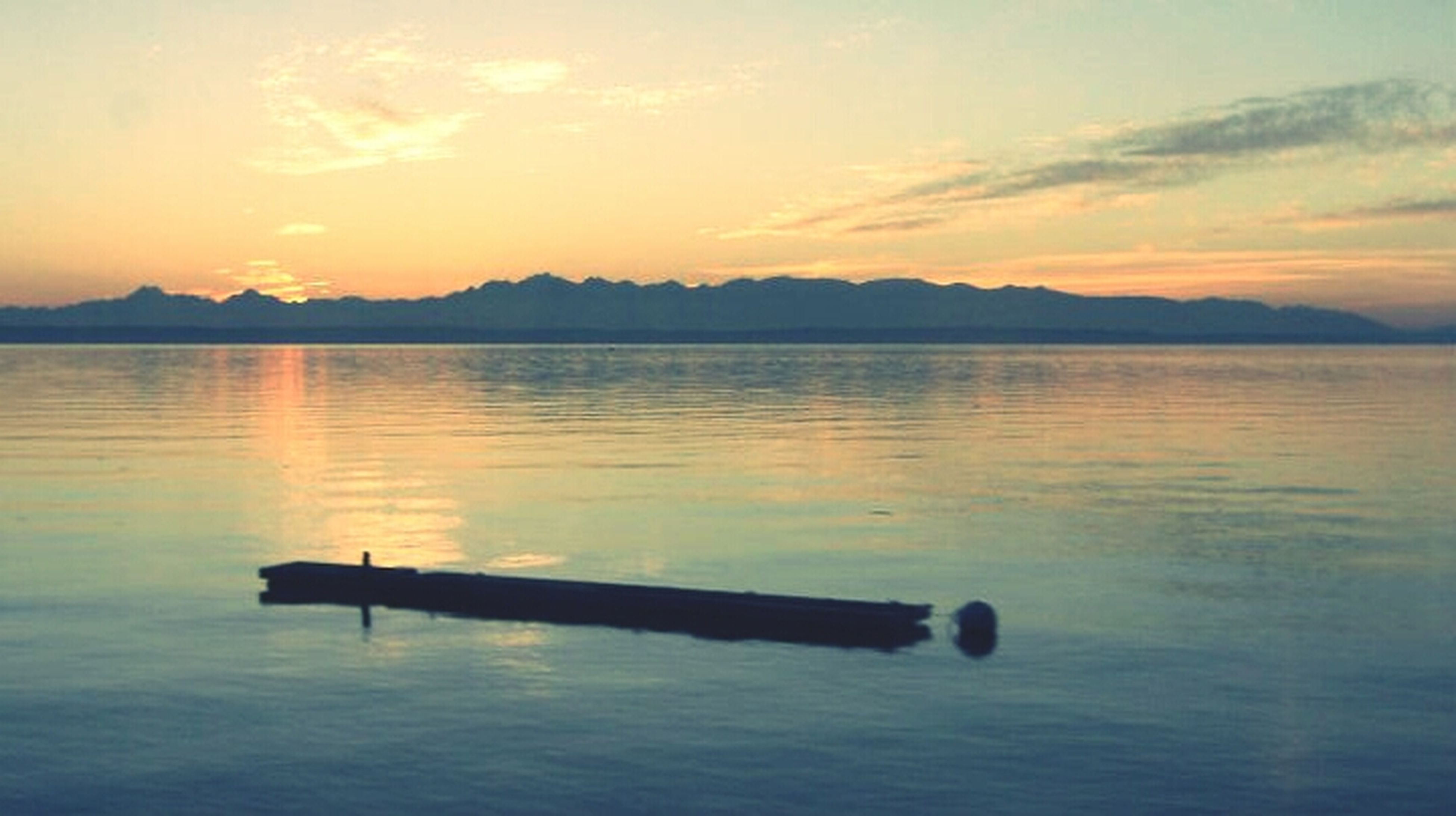 sunset, water, tranquil scene, tranquility, scenics, reflection, lake, beauty in nature, orange color, sky, idyllic, silhouette, nature, waterfront, mountain, sea, calm, rippled, outdoors, non-urban scene