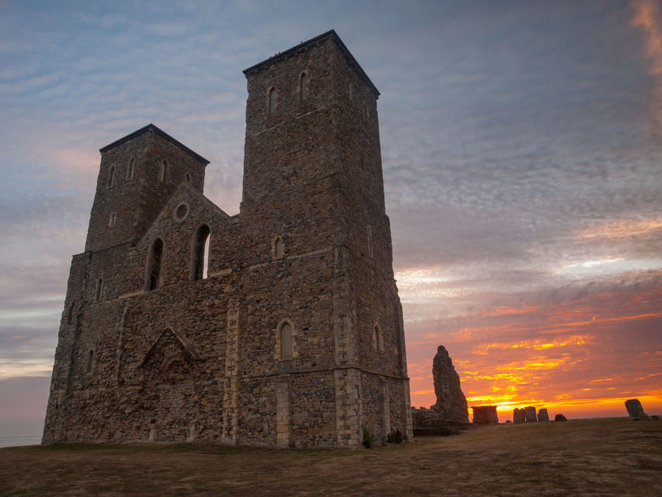 Reculver is a village and coastal resort about 3 miles (5 km) east of Herne Bay in south-east England, in a ward of the same name, in the City of Canterbury district of Kent. It once occupied a strategic location at the north-western end of the Wantsum Channel, a sea lane that separated the Isle of Thanet and the Kent mainland until the late Middle Ages. This led the Romans to build a small fort there at the time of their conquest of Britain in 43 AD, and, starting late in the 2nd century, they built a larger fort, or castrum, called Regulbium, which later became one of the chain of Saxon Shore forts. The military connection resumed in the Second World War, when the sea off Reculver was used for testing Barnes Wallis's bouncing bombs. Architecture Kent No People Outdoors Reculver Reculver Towers Sky Sunset Travel Travel Destinations Vivid International