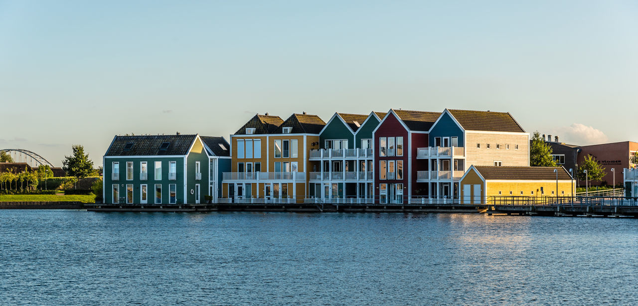 Residential houses in Netherlands Architecture Building Exterior Built Structure Colorful Colorful Houses Day Development Dusk House Housing In A Row Outdoors Painted Pond Rainbow Rainbow Colors Real Estate Residential Building Residential District Residential Structure Row House Sky Sunset Water Waterfront