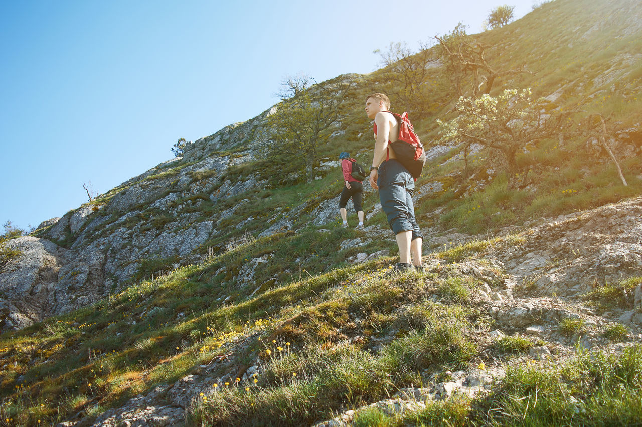 Man looks into the distance on the mountain Adult Adventure Beauty In Nature Casual Clothing Clear Sky Climbing Day Hiking Landscape Leisure Activity Low Angle View Mountain Nature Outdoors People RISK Sky Standing Tourist Young Adult Young Women