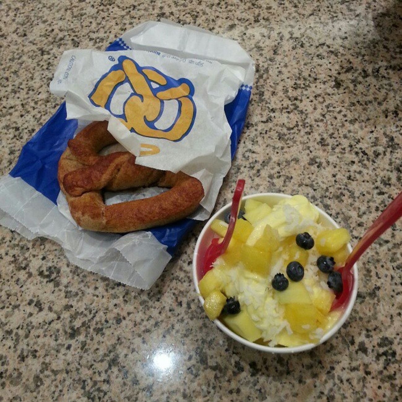 Nom nom nom. Redmango Mango Yogurt with pineapple blueberries coconut shavings and auntieannes pretzel with my girl eno..