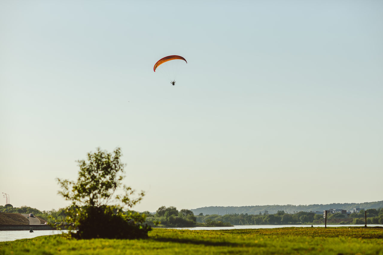 Paragliding Adventure Beauty In Nature Clear Sky Day Evening Extreme Sports Flying Grass Leisure Activity Mid-air Nature One Person Outdoors Parachute Paragliding Paragliding People Pilot Real People Recreational  Sky Sport Tree