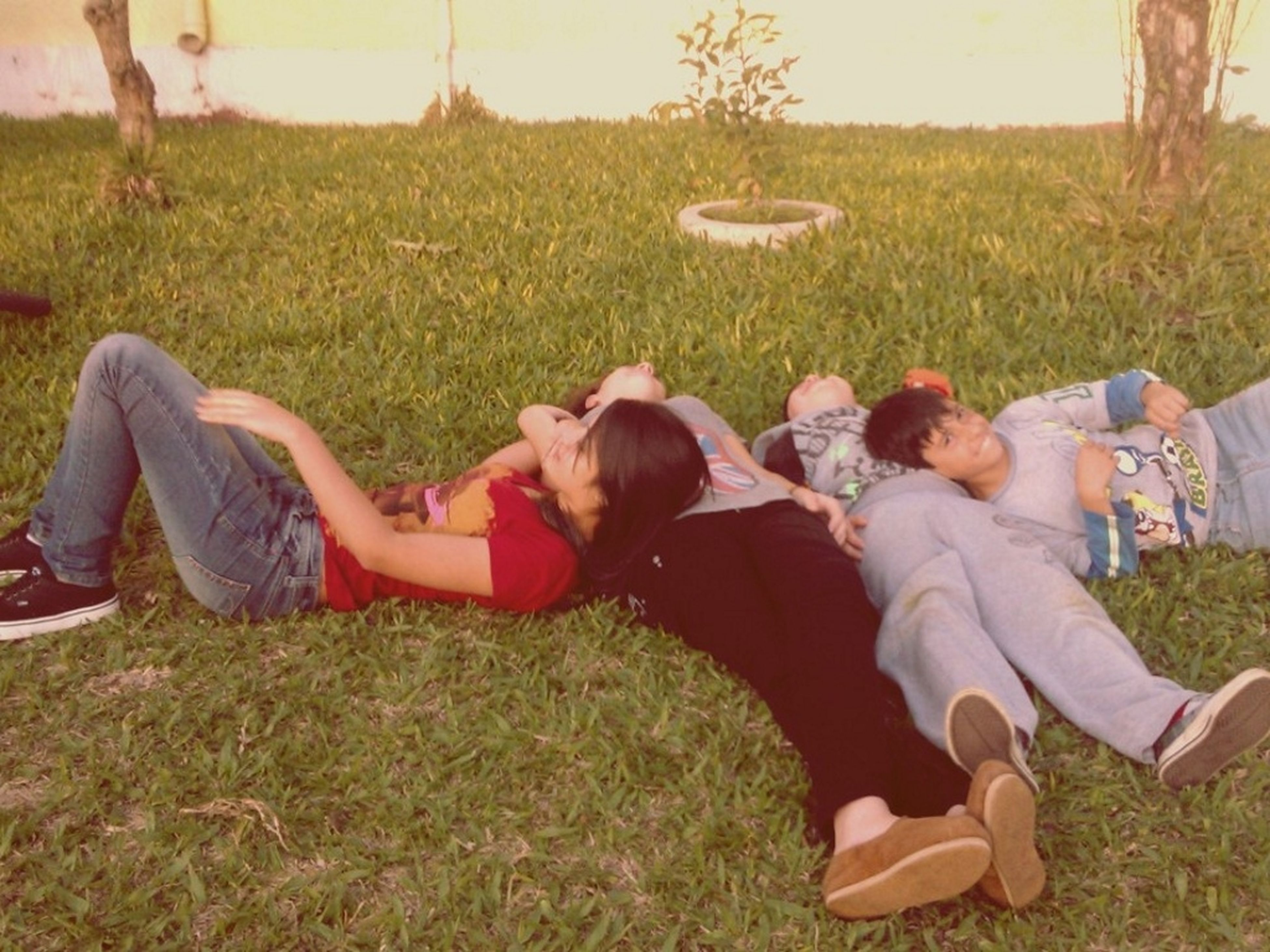 grass, sitting, relaxation, leisure activity, togetherness, lifestyles, bonding, field, casual clothing, love, resting, lying down, person, friendship, grassy, men, relaxing
