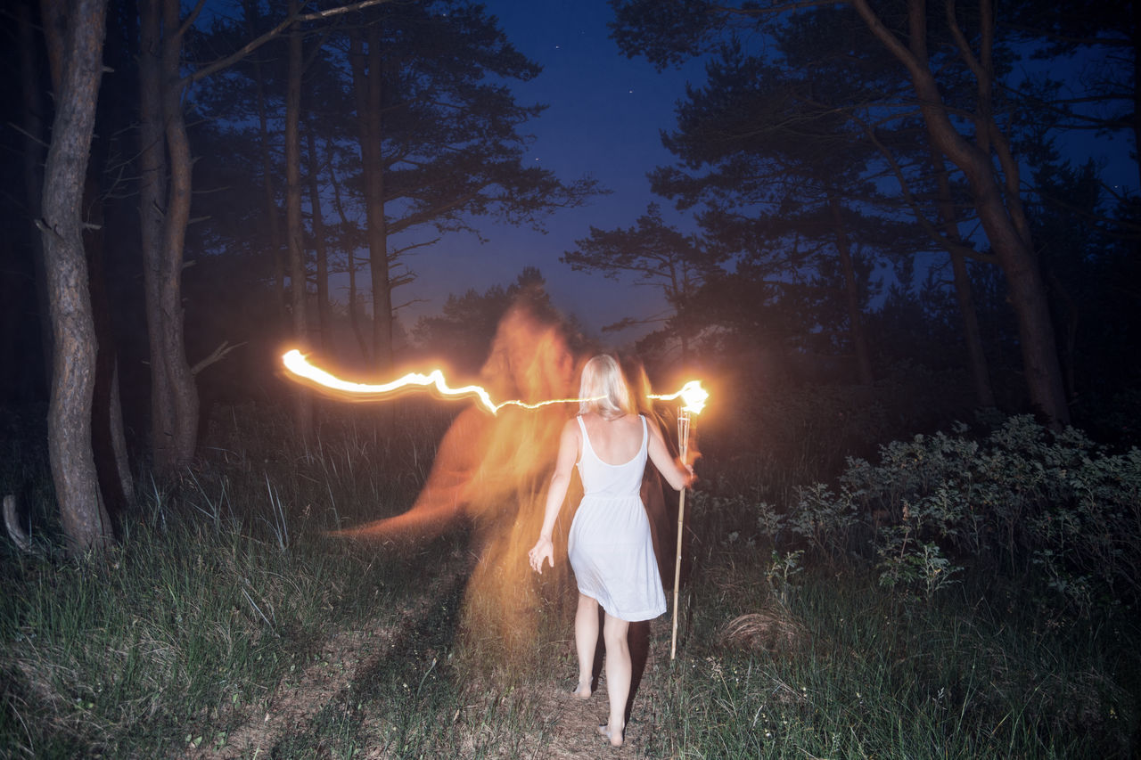 Rear View Of Woman Walking With Flaming Torch In Forest At Night