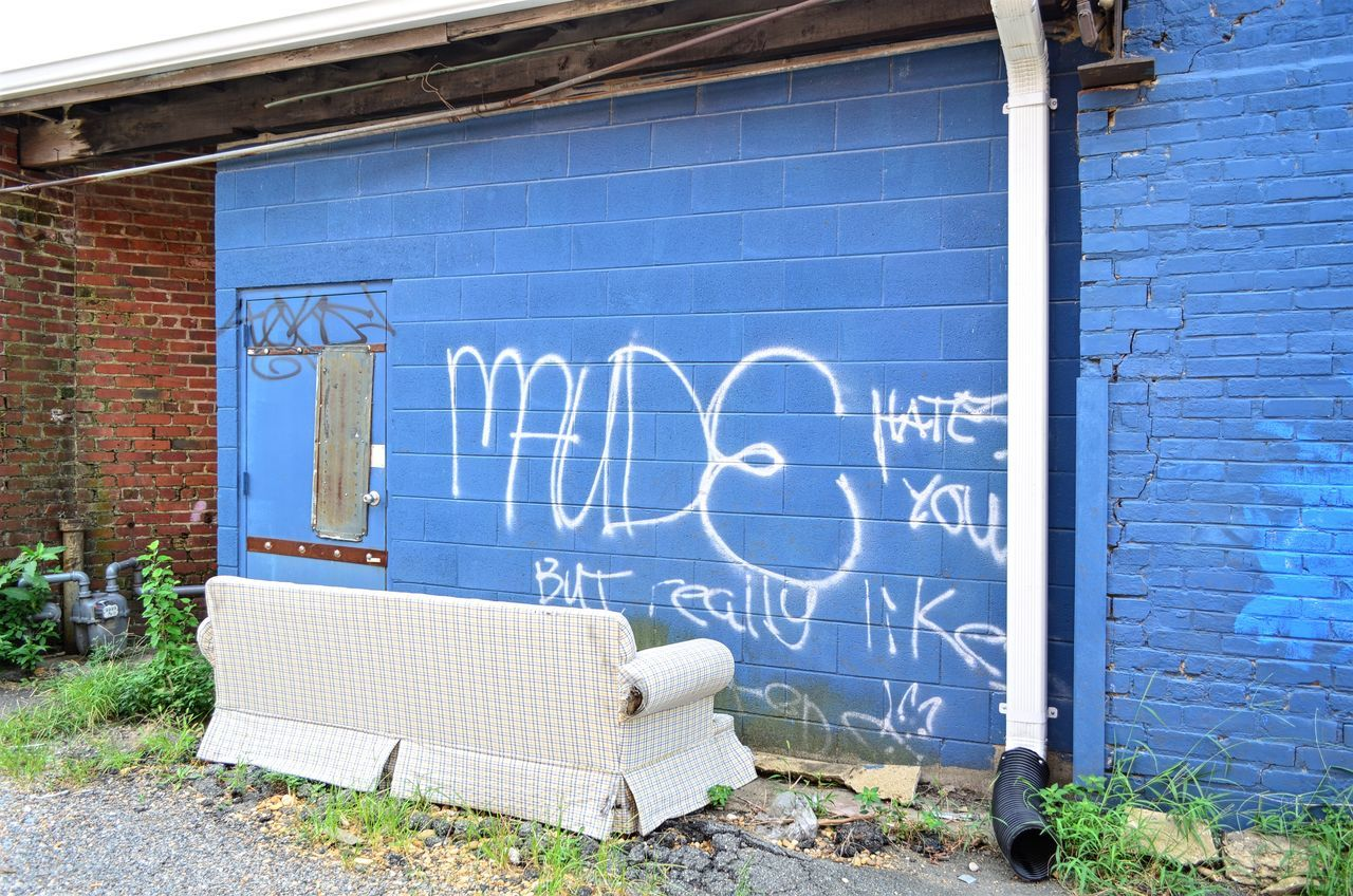 Graffiti in alley with discarded sofa Alley Blue Building Exterior Built Structure Day Discarded Graffiti No People Outdoors Pjpink Sofa Text