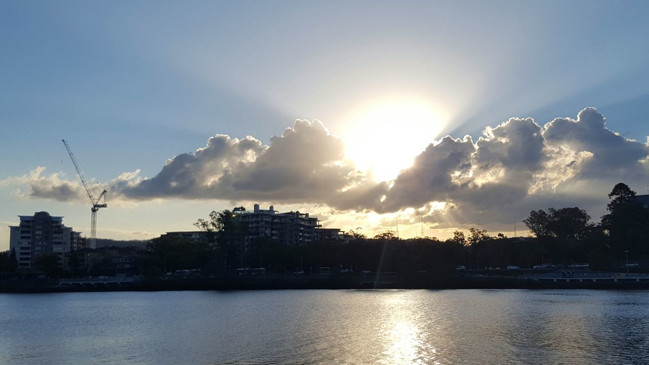 sky, sunset, sunlight, sunbeam, sun, waterfront, beauty in nature, water, nature, river, outdoors, cloud - sky, no people, reflection, scenics, tranquil scene, tranquility, built structure, travel destinations, tree, architecture, building exterior, day