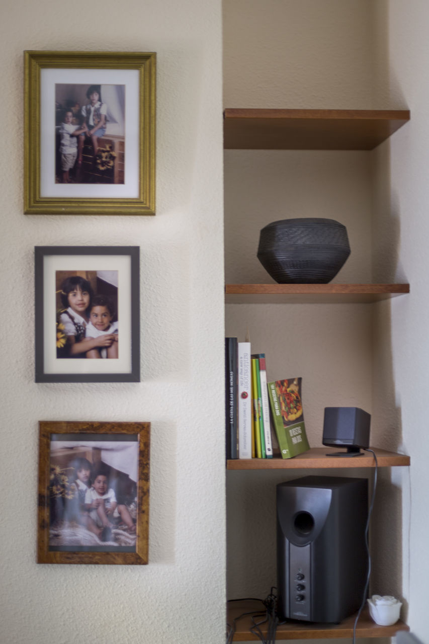 picture frame, human representation, male likeness, indoors, art and craft, female likeness, no people, sculpture, home interior, statue, close-up, architecture, bookshelf, day