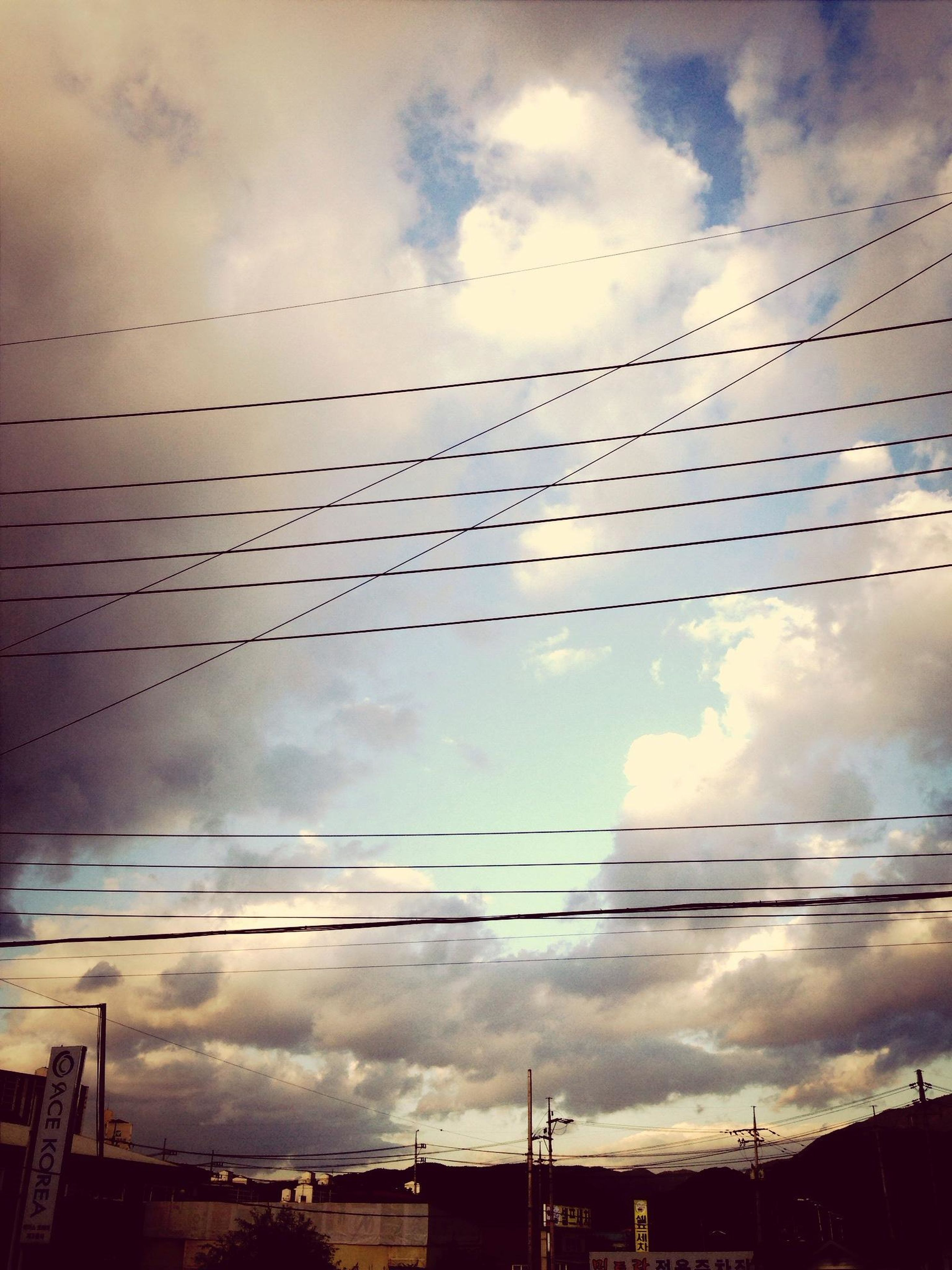 low angle view, sky, cloud - sky, architecture, built structure, cloudy, building exterior, power line, cloud, bird, silhouette, cable, connection, dusk, overcast, weather, outdoors, no people, electricity, building