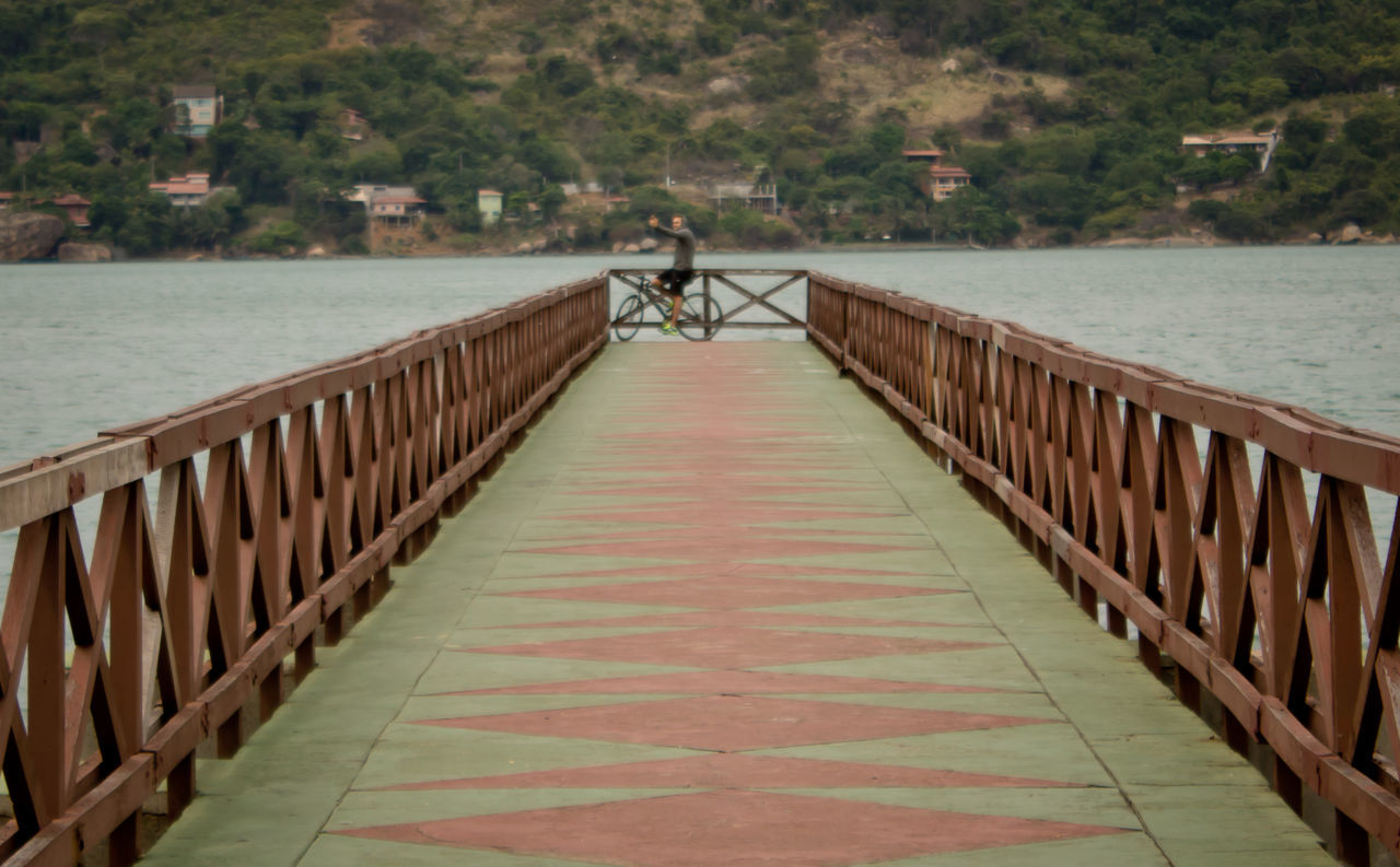 Man On Bicycle Over Pier At Lake