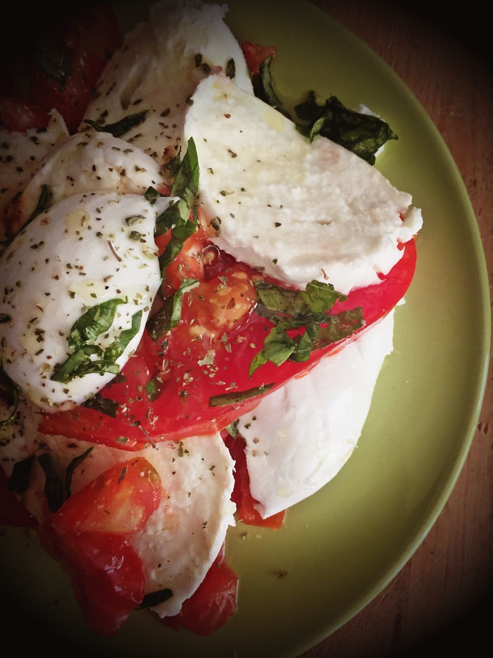 Top View Of Tomato And Cheese Salad Garnished With Basil Leaves And Herbs