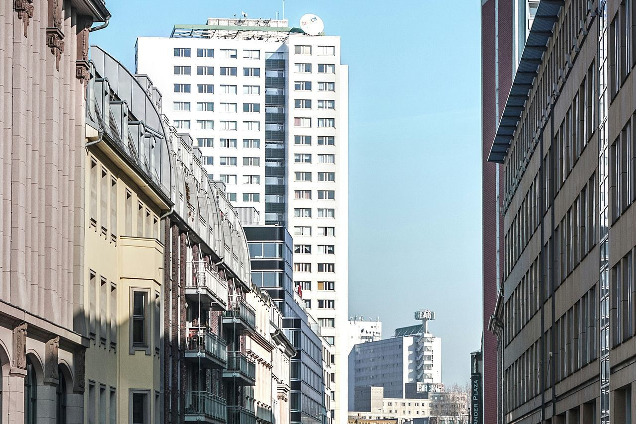 building exterior, architecture, city, window, built structure, clear sky, day, no people, residential building, sunlight, low angle view, outdoors, skyscraper, sky, cityscape