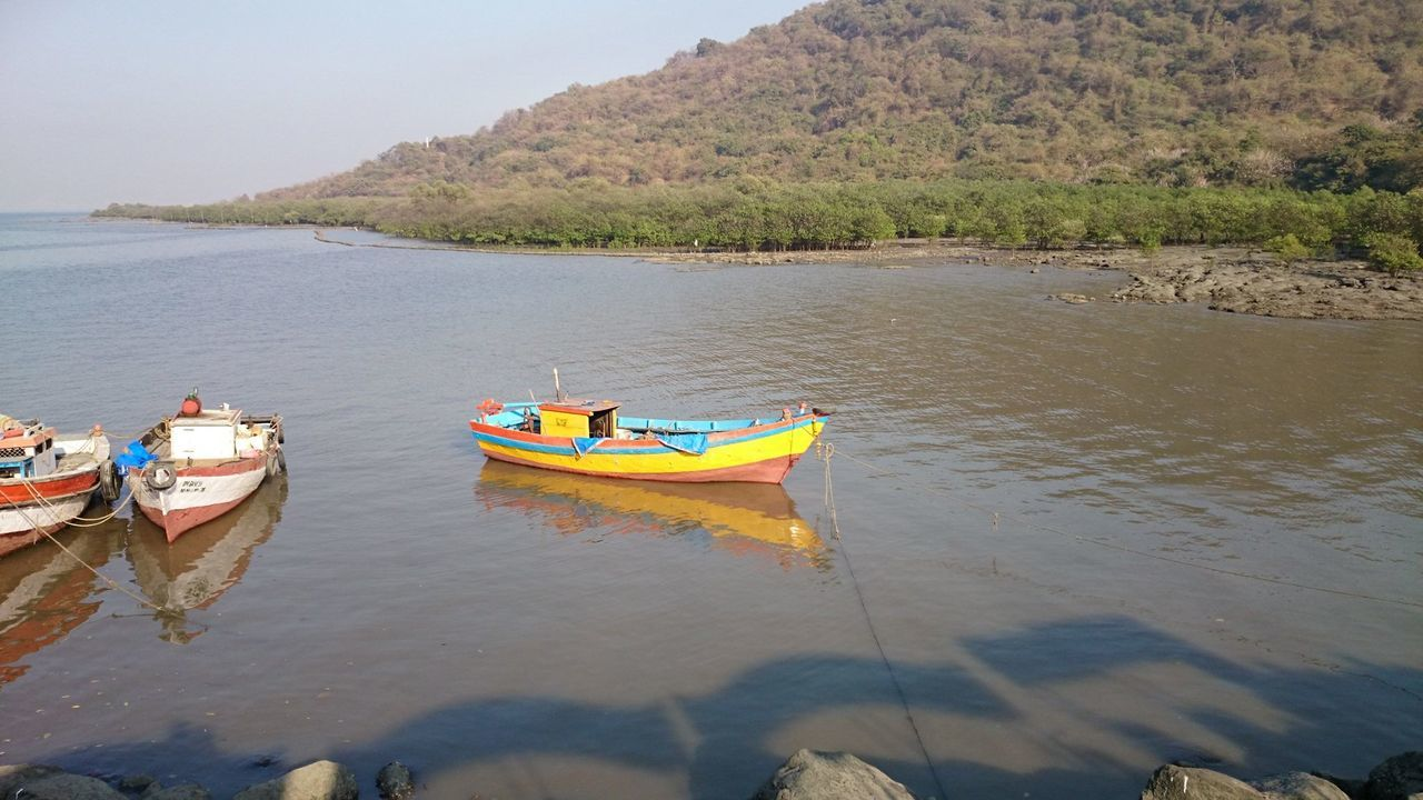 Boats Moored In Calm River Against Mountain