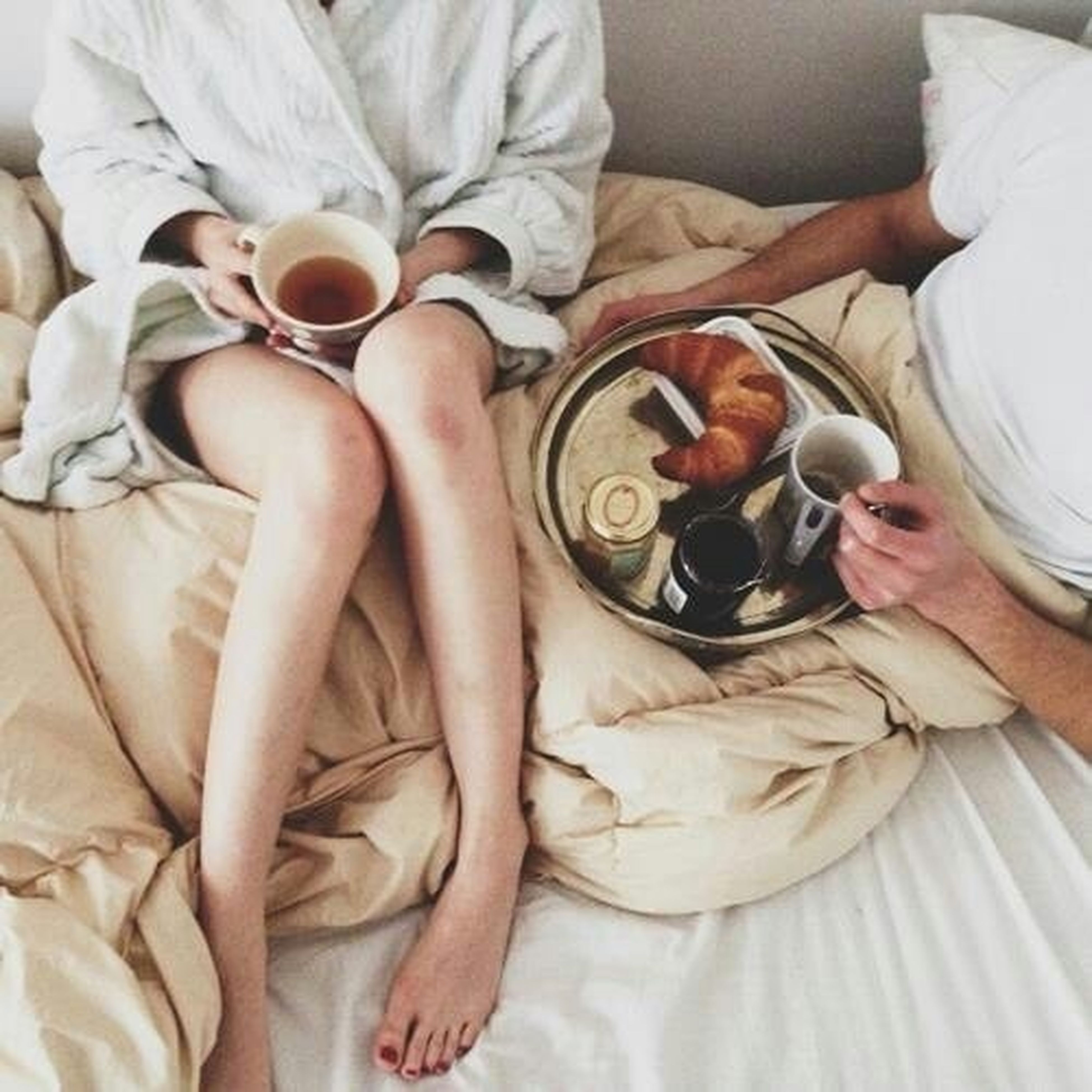 indoors, bed, high angle view, relaxation, table, sitting, home interior, bedroom, pillow, food and drink, lifestyles, casual clothing, person, blanket, midsection, men, holding