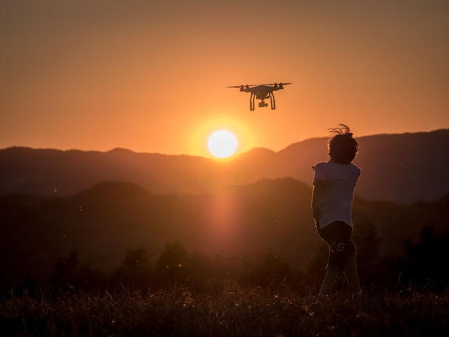 Drone into the sunset Beauty In Nature Boy Drone  Evening Field Flyng Grass Hills Insects  Landscape Leisure Activity Lifestyles Mosquito Mountain Nature Orange Color Outdoors Phantom Shadow Sky Summer Sun Sunset Color Palette A Bird's Eye View