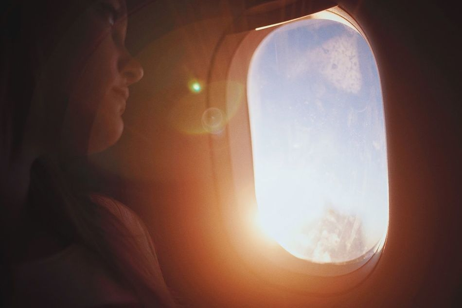 On the way home. Window Transparent Sun Transportation Sky Flying Lens Flare Air Vehicle Scenics Traveling Blonde Woman Girl Windows Plane Travel Travel Destinations The Week Of Eyeem TakeoverContrast Sunbeam Traveling Home For The Holidays My Year My View Adventure Tourism 35mm