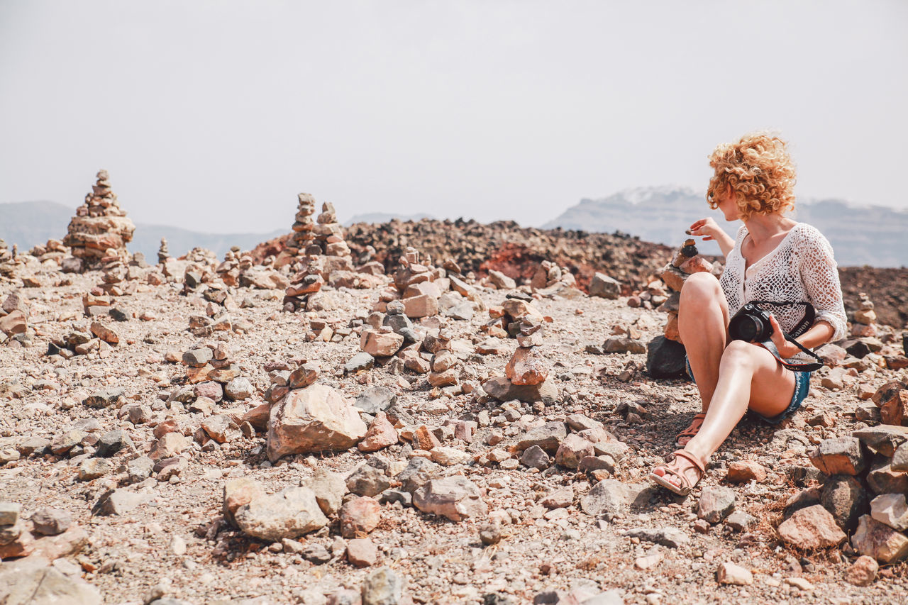 Woman Sitting On Rocky Landscape