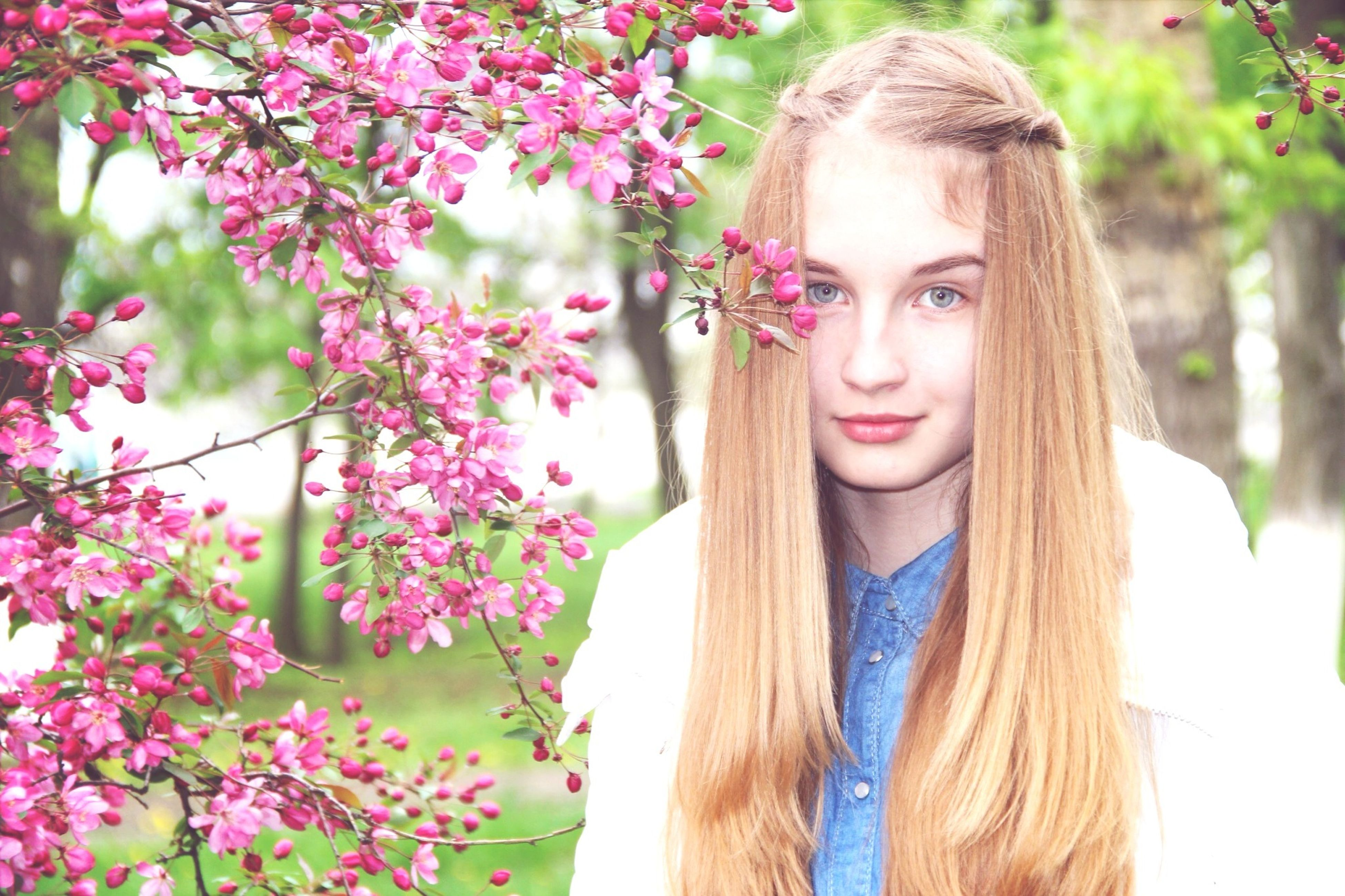 young adult, young women, person, smiling, looking at camera, portrait, front view, lifestyles, long hair, flower, leisure activity, casual clothing, happiness, tree, standing, focus on foreground, toothy smile