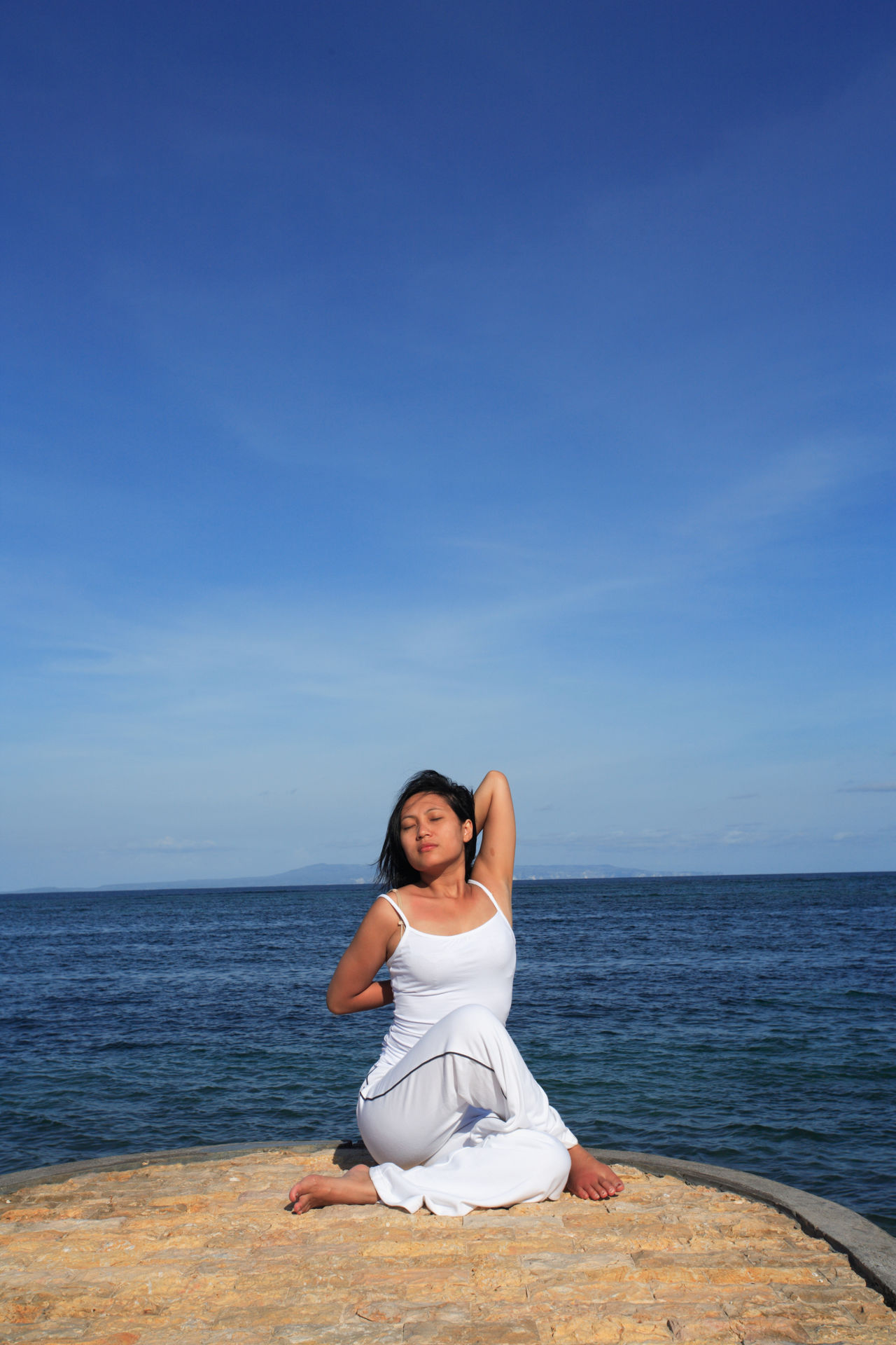 Adult Adults Only Beach Blue Females Full Length Horizon Over Water Human Body Part Lifestyles One Person One Woman Only Only Women Outdoors People Relaxation Relaxation Exercise Sand Sea Serene People Sitting Sky Summer Vacations Women Yoga