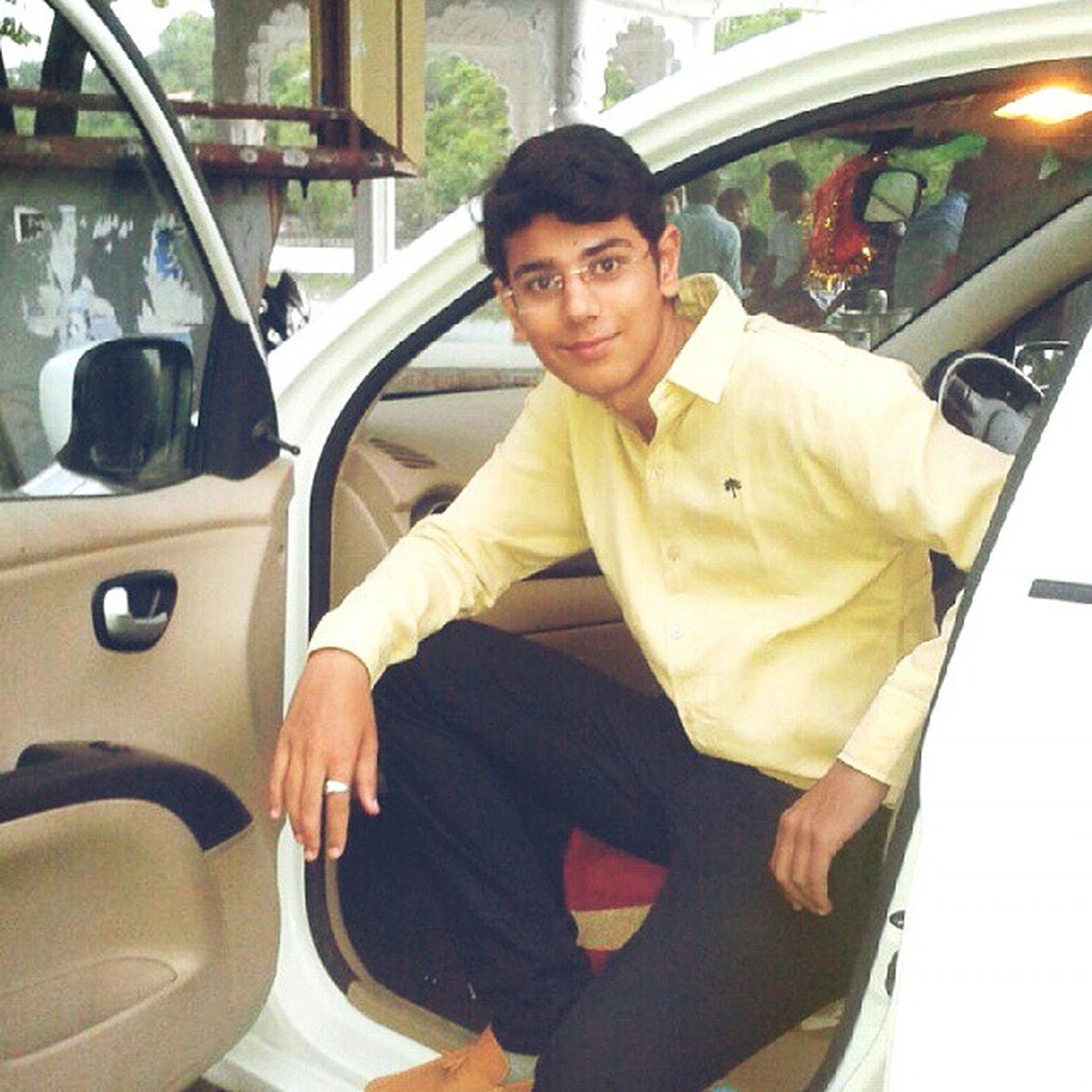 young adult, person, lifestyles, transportation, casual clothing, portrait, mode of transport, looking at camera, leisure activity, young men, front view, sitting, land vehicle, sunglasses, smiling, indoors, car, three quarter length
