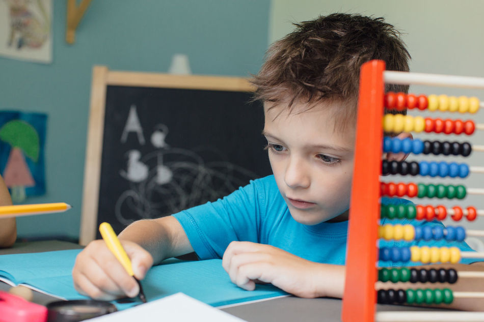 Schoolboy working on math homework with an abacus Abacus Assignment Boy Caucasian Child Counting Critical Home Homeschooling Homework Independent  Kid Learn Learning Mathematics Maths Project Room School Schoolboy Schoolchild Solitary Student Thinking Young