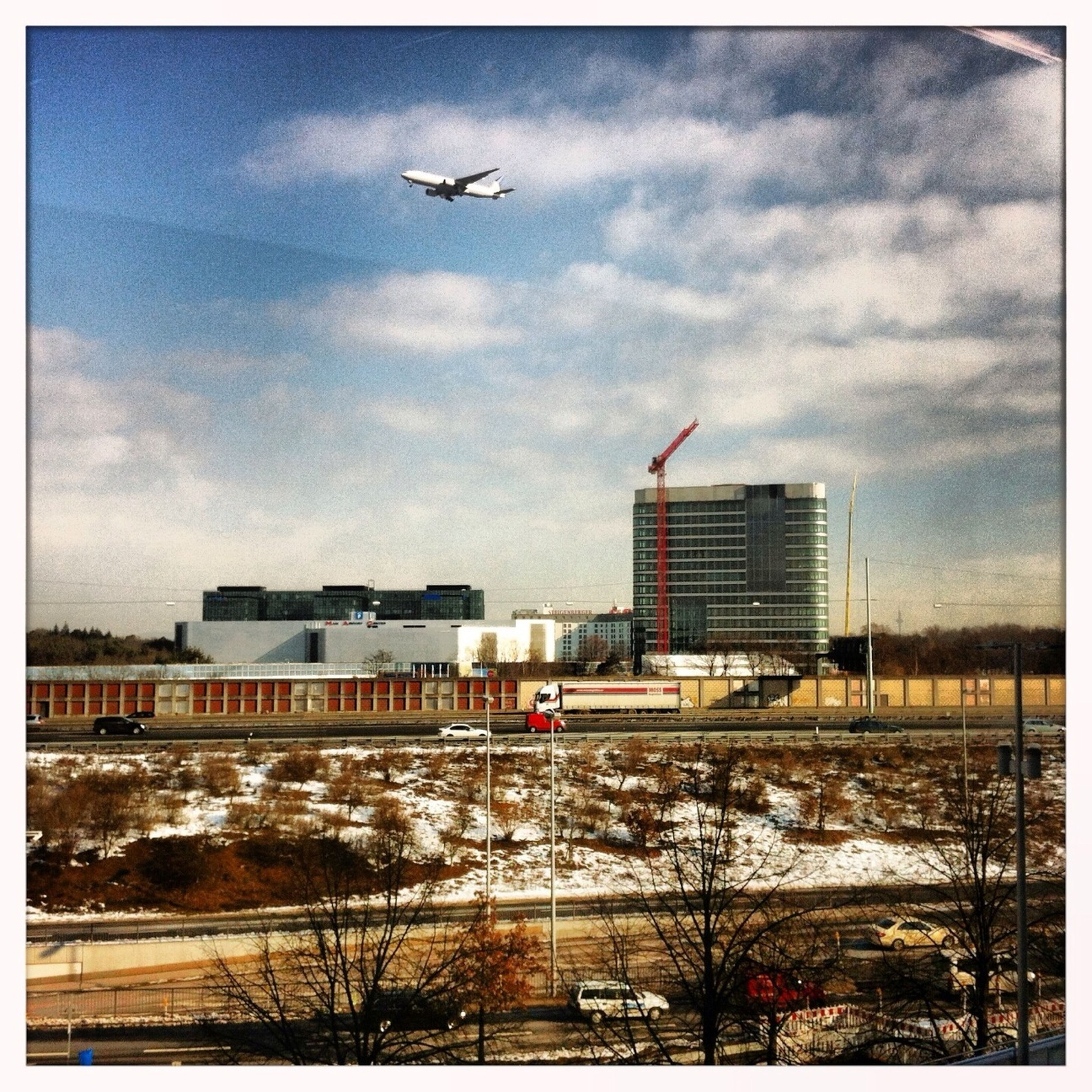 transfer print, building exterior, flying, built structure, auto post production filter, architecture, sky, transportation, cloud - sky, bird, mode of transport, snow, city, winter, weather, cloud, cold temperature, cloudy, animal themes, public transportation