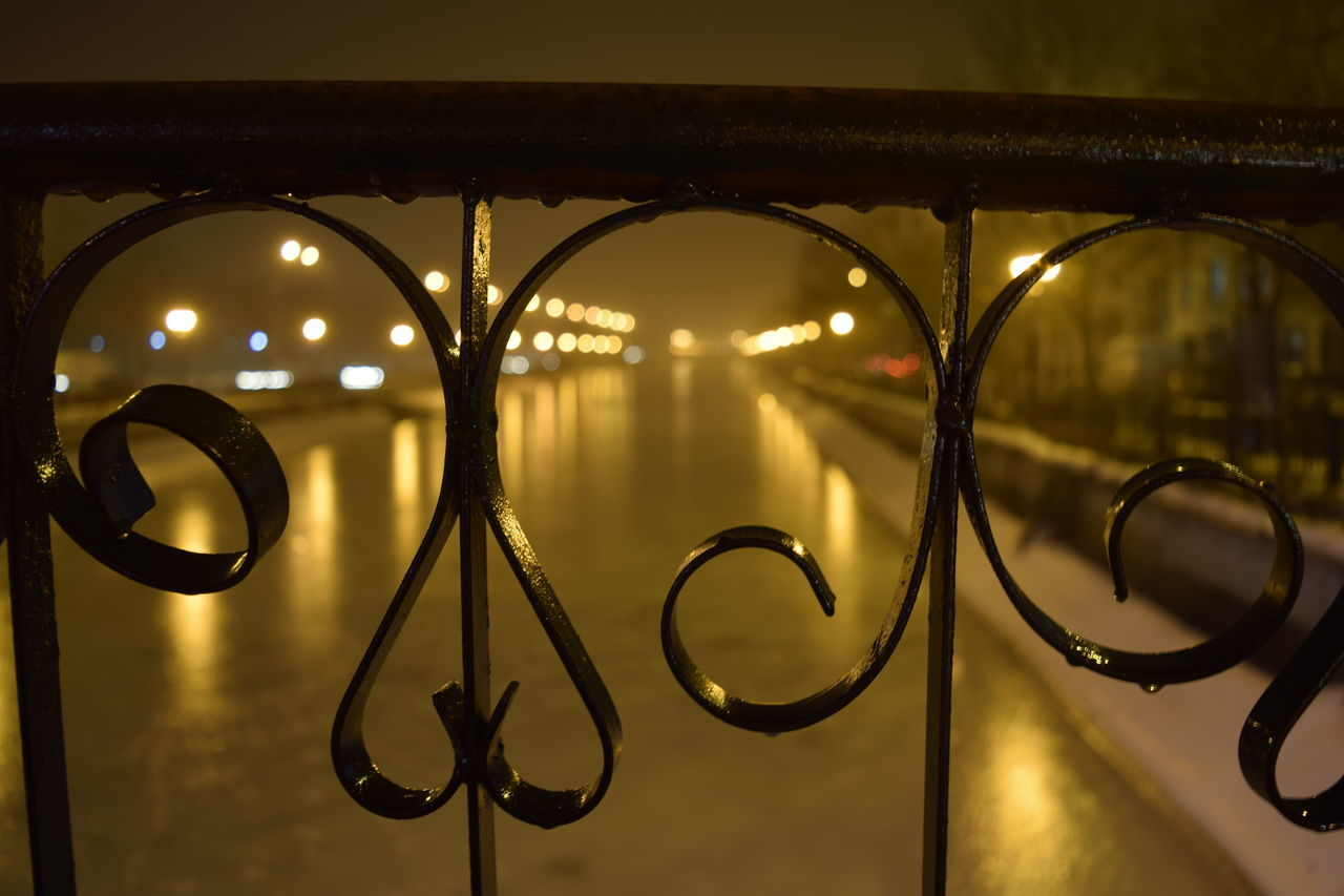 Lit Lights Along Blurred Lake With Railings In Foreground
