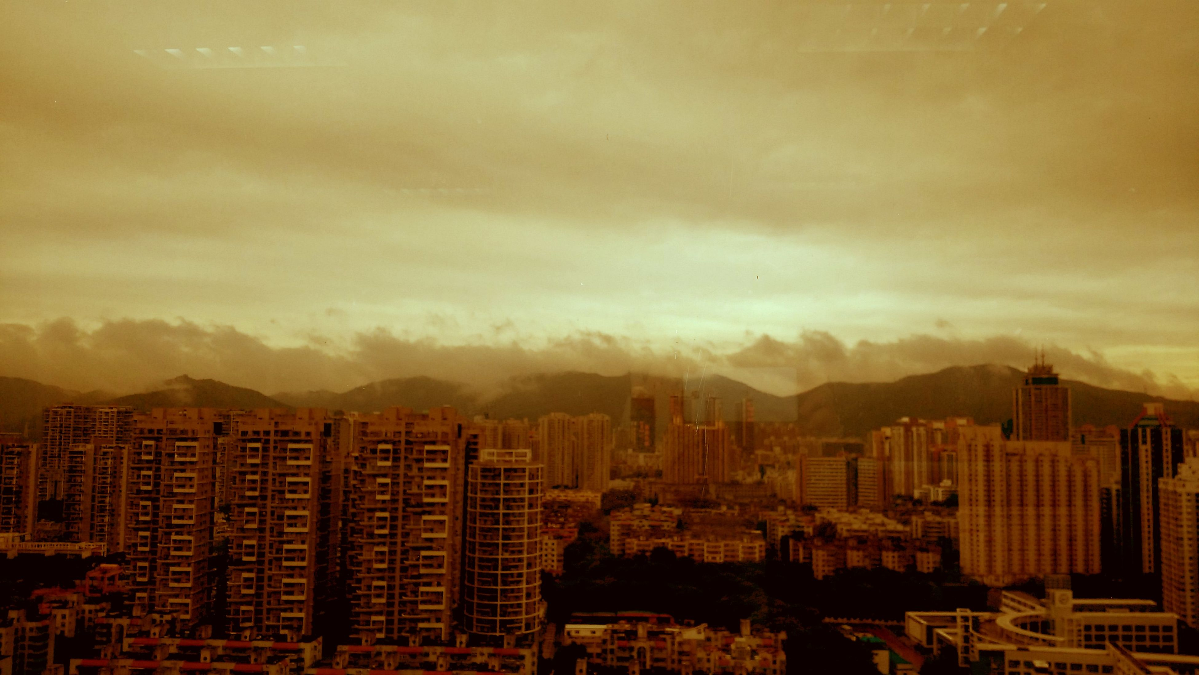 building exterior, architecture, built structure, city, cityscape, sky, mountain, sunset, cloud - sky, residential building, residential district, mountain range, high angle view, residential structure, skyscraper, crowded, no people, outdoors, dusk, city life