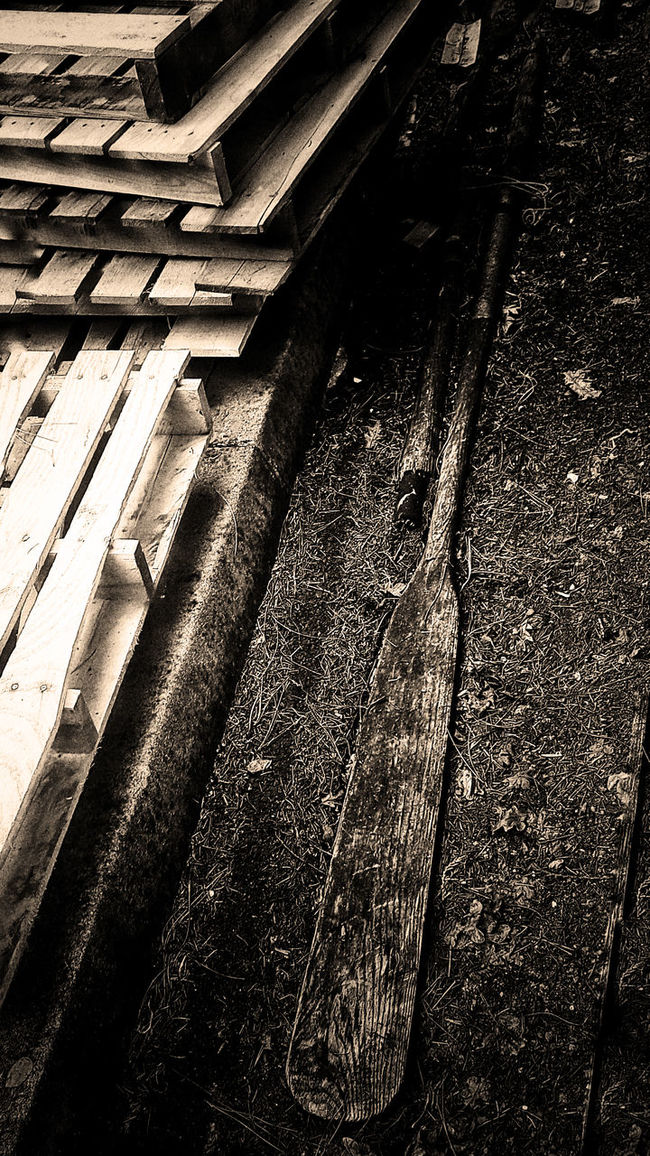 Pile of old wood soda crates stacked up next to a curb, along with a couple of old wooden oars. Wooden Crates Wood Crate Wood Material Palettes Pallet Pallete Palette Oars Old Curb Curbside By The Curb Garbage Pile Sepia Tone Sepia Found Objects Monochromatic Outdoors Outside Still Life Crates Wood Boxes Pile Of Crates