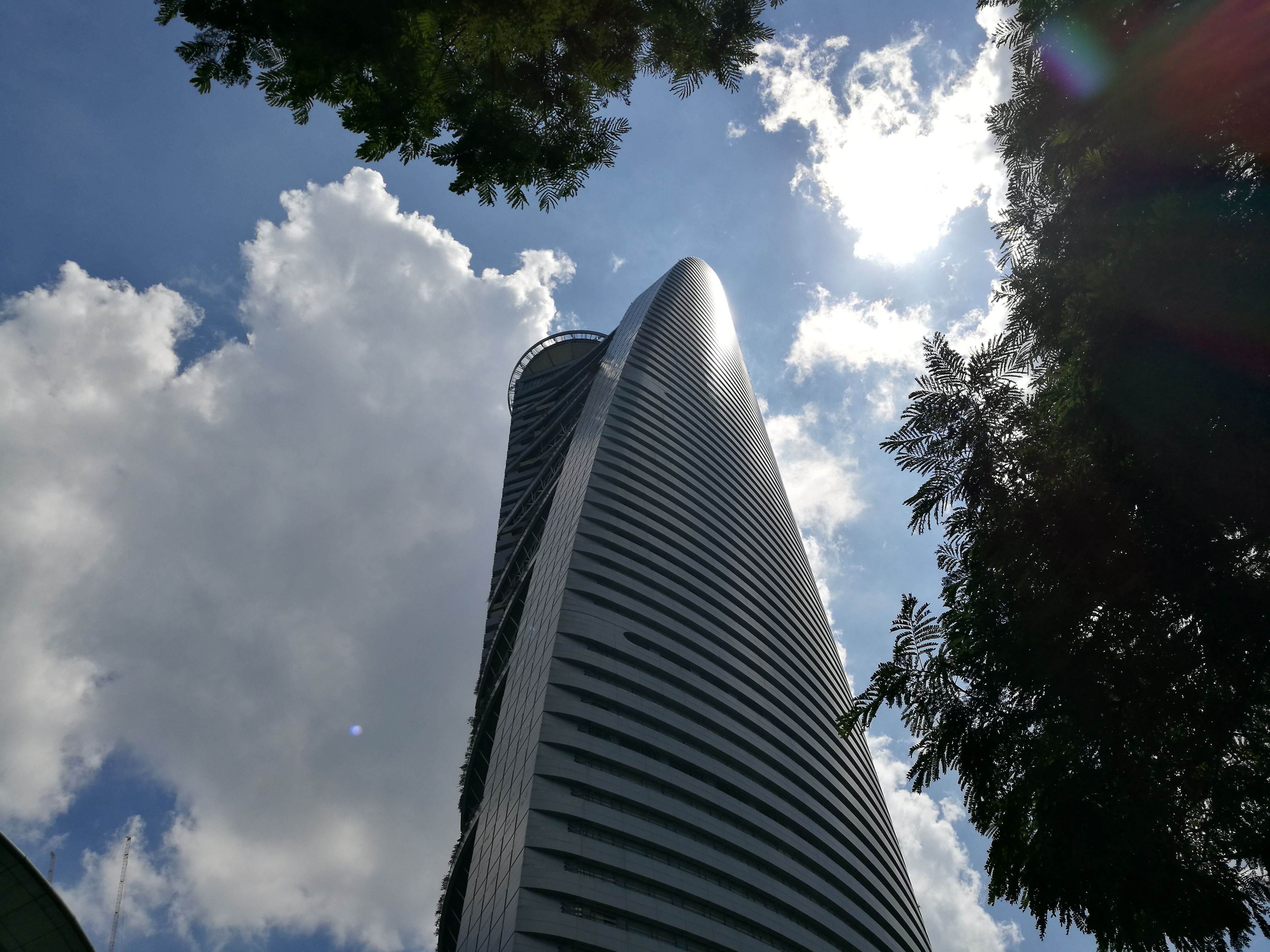 low angle view, skyscraper, sky, tall - high, tower, architecture, city, modern, building exterior, built structure, tree, cloud - sky, office building, growth, sun, day, cloud, outdoors, tall, bright, diminishing perspective, city life