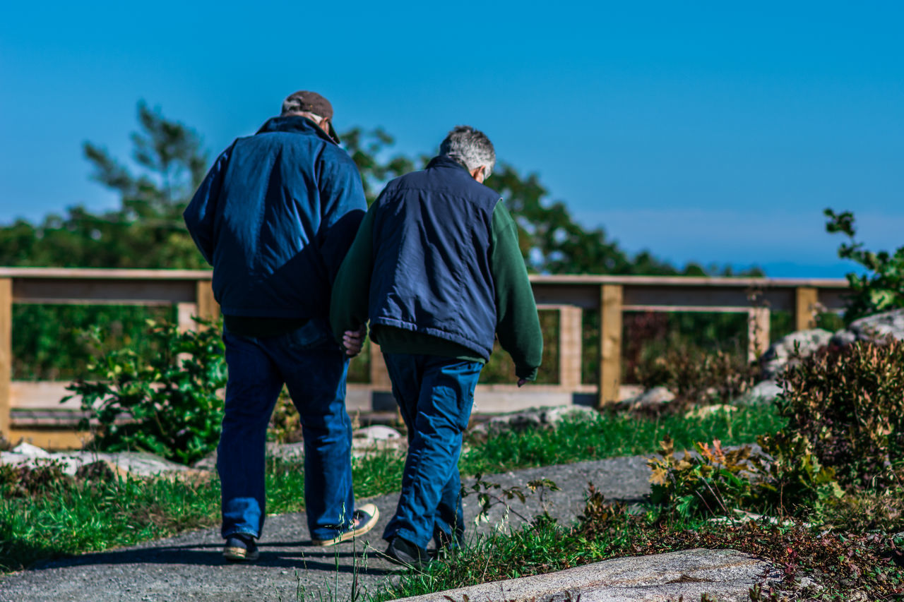 Architecture Blue Casual Clothing Couple Day Focus On Foreground Footpath Full Length Holding Hands Leisure Activity Old Couple In Love Outdoors Plant Rear View Sunlight Togetherness