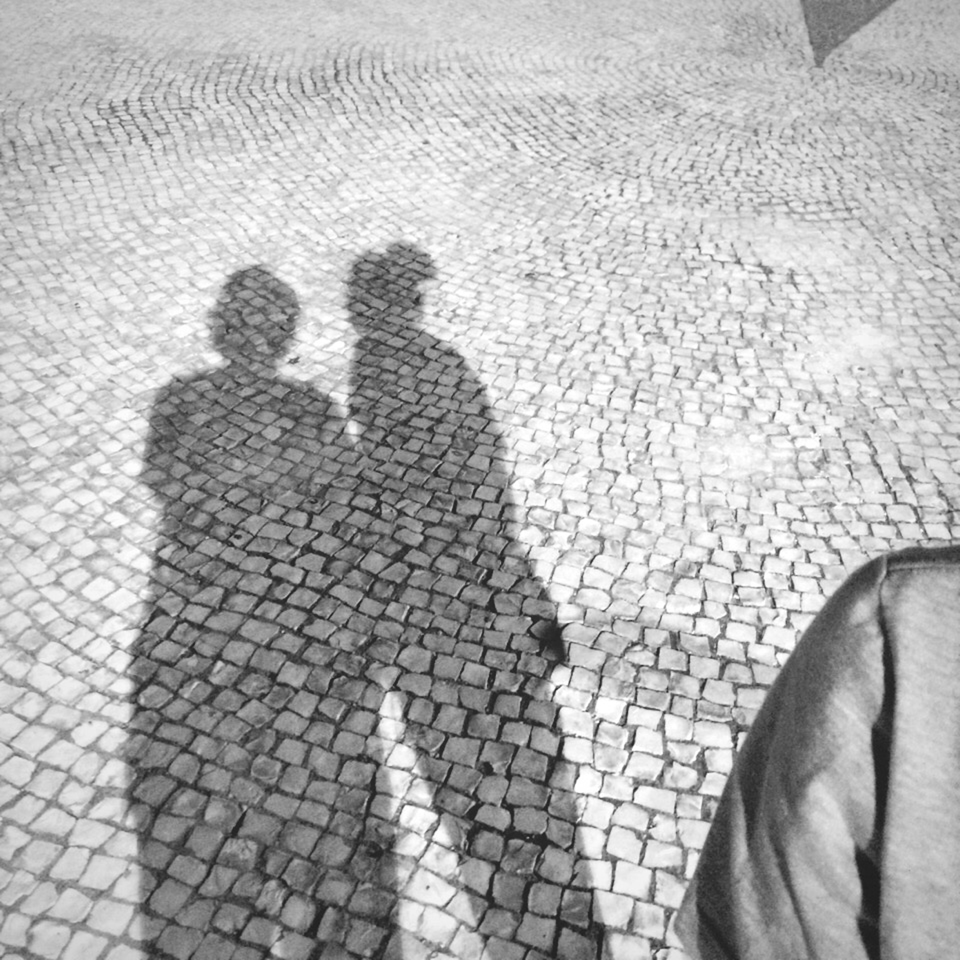 shadow, men, focus on shadow, high angle view, lifestyles, unrecognizable person, togetherness, leisure activity, street, cobblestone, sunlight, bonding, day, love, outdoors, standing, pattern