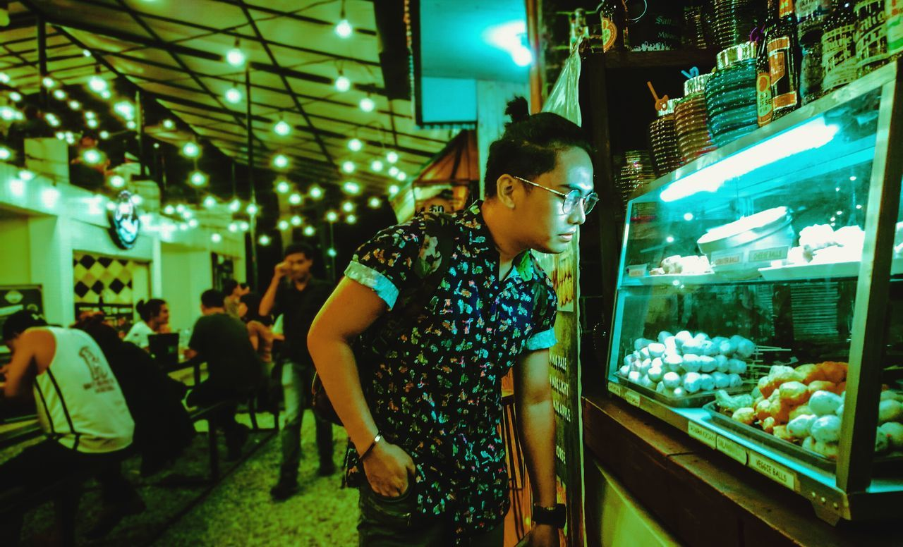 Streetfood. 📷 Night Illuminated Standing Nightlife One Person Young Adult Side View Real People Indoors  Lifestyles Young Women Neon Nightclub City Food People Adult Adults Only Streetphotography FoodPark