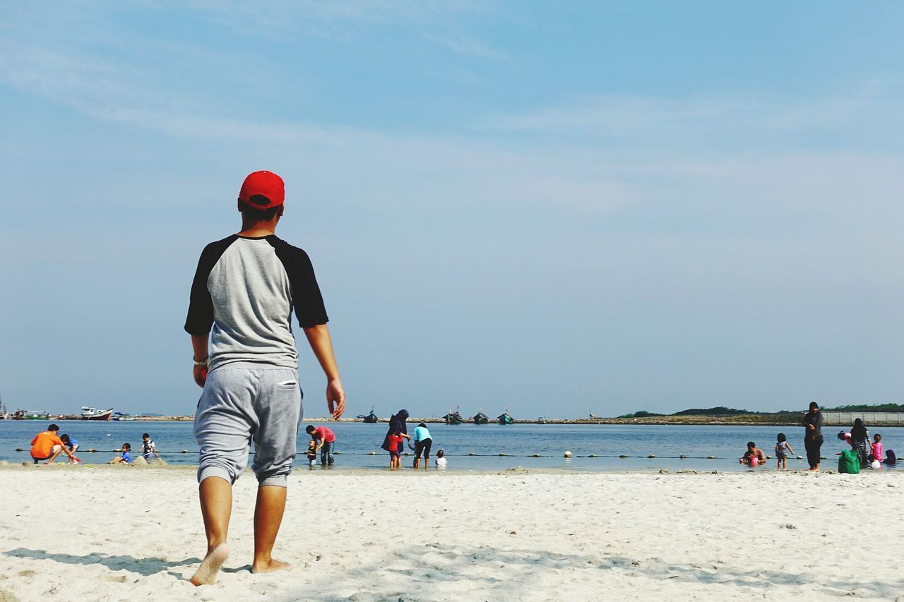 real people, rear view, beach, incidental people, sand, sea, men, lifestyles, water, leisure activity, day, nature, one person, sunlight, walking, sky, outdoors, vacations, scenics, beauty in nature, standing, horizon over water, full length, mammal, people