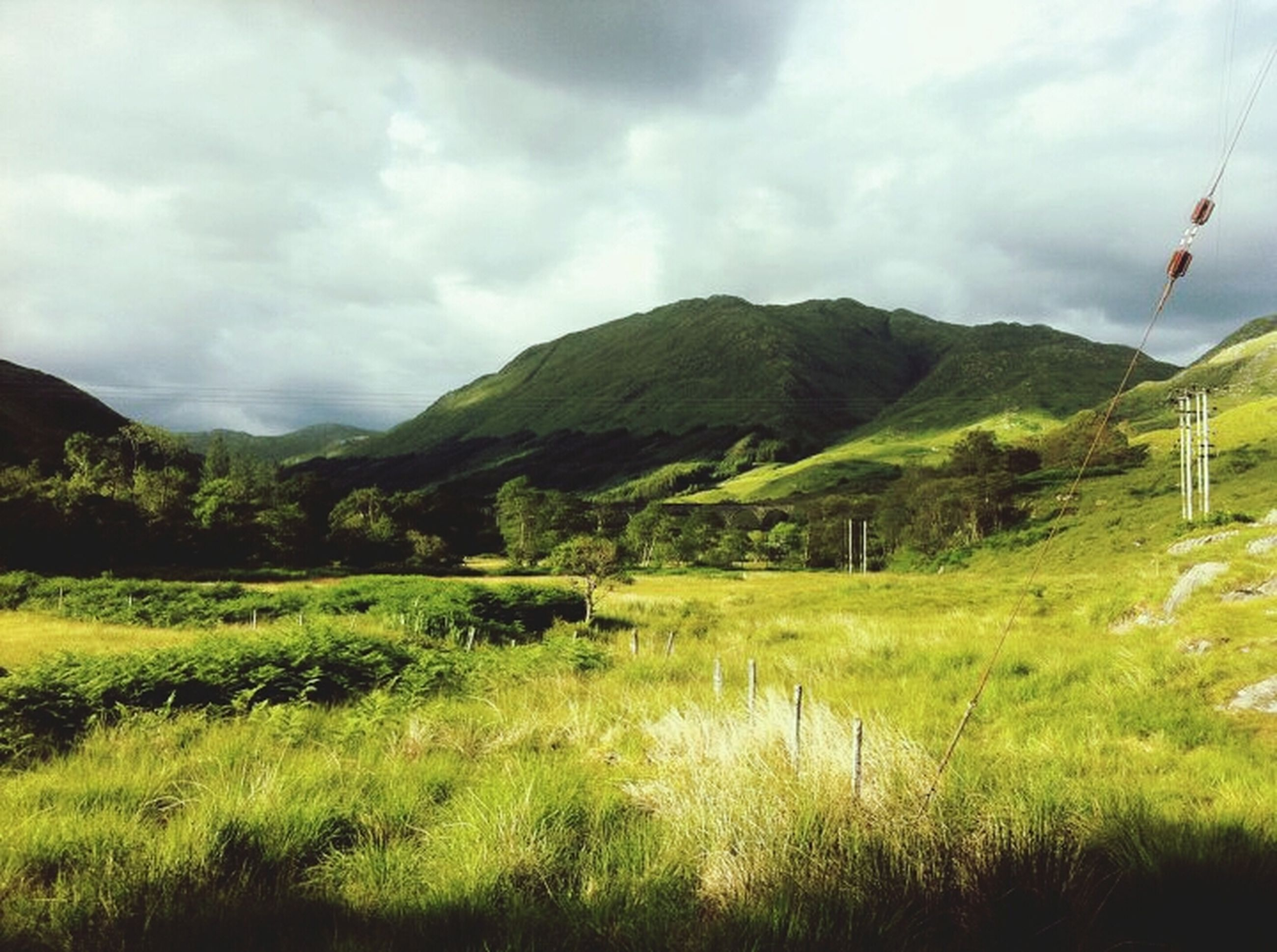 mountain, sky, cloud - sky, mountain range, grass, cloudy, tranquil scene, landscape, scenics, tranquility, beauty in nature, cloud, nature, green color, non-urban scene, hill, day, idyllic, field, weather