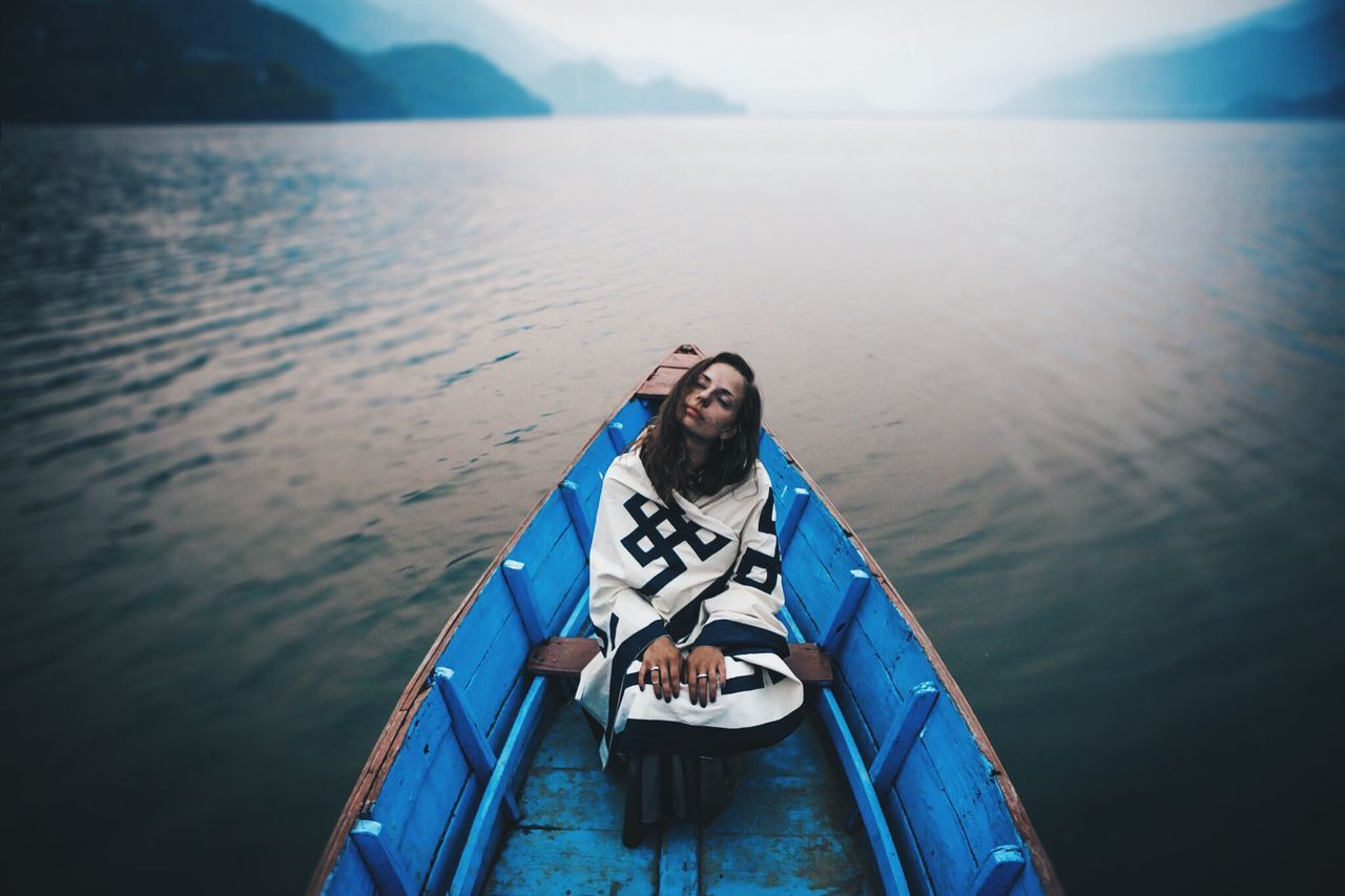 Full Length Of Woman Sailing In Blue Rowboat In River