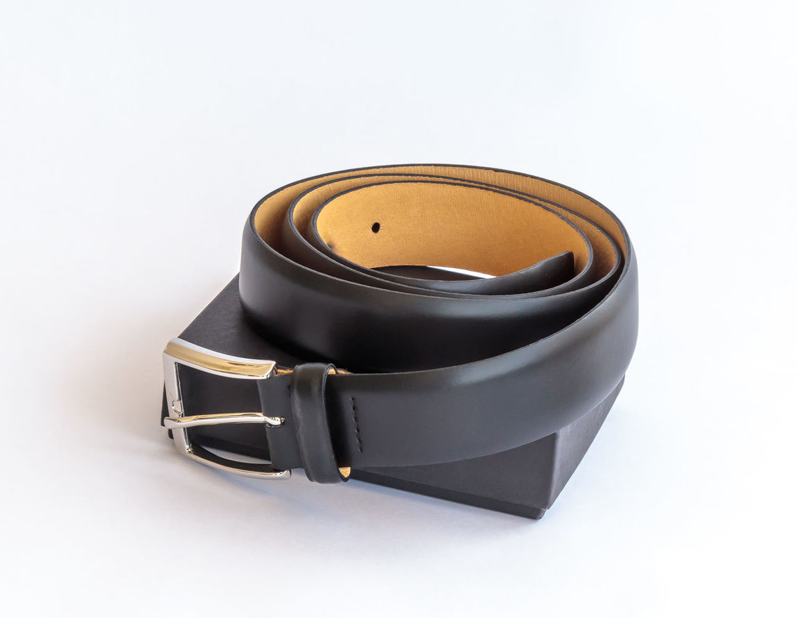 Black leather belt with metal buckle and its black cardboard packing box on a white background Accessory Belt  Black Box Buckle Cardboard Close-up Cloth Design Elegant Fashion Gift Isolated Leather Men Metal Modern Pack Personal Roll Silver  Single Studio Shot Style White Background
