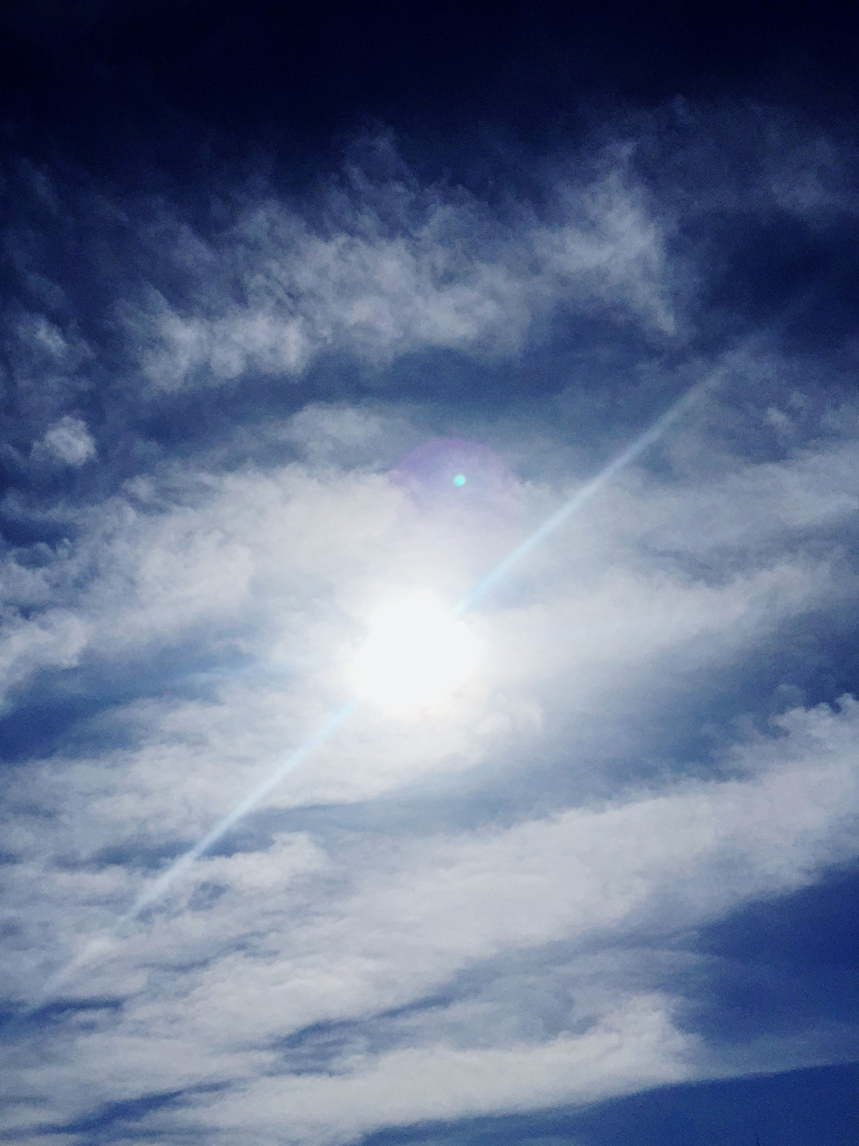 low angle view, sky, sun, cloud - sky, sunbeam, beauty in nature, sky only, tranquility, blue, sunlight, nature, scenics, tranquil scene, lens flare, cloud, backgrounds, cloudy, idyllic, cloudscape, vapor trail