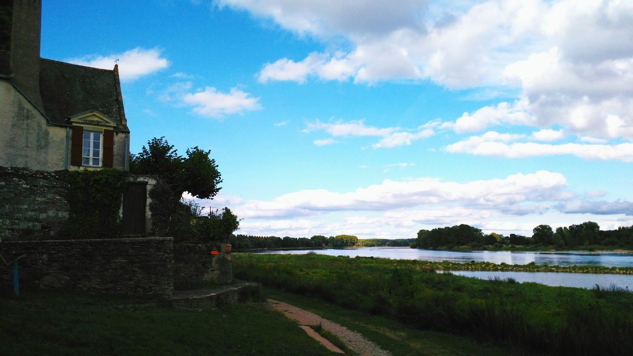 House By River Against Blue Sky