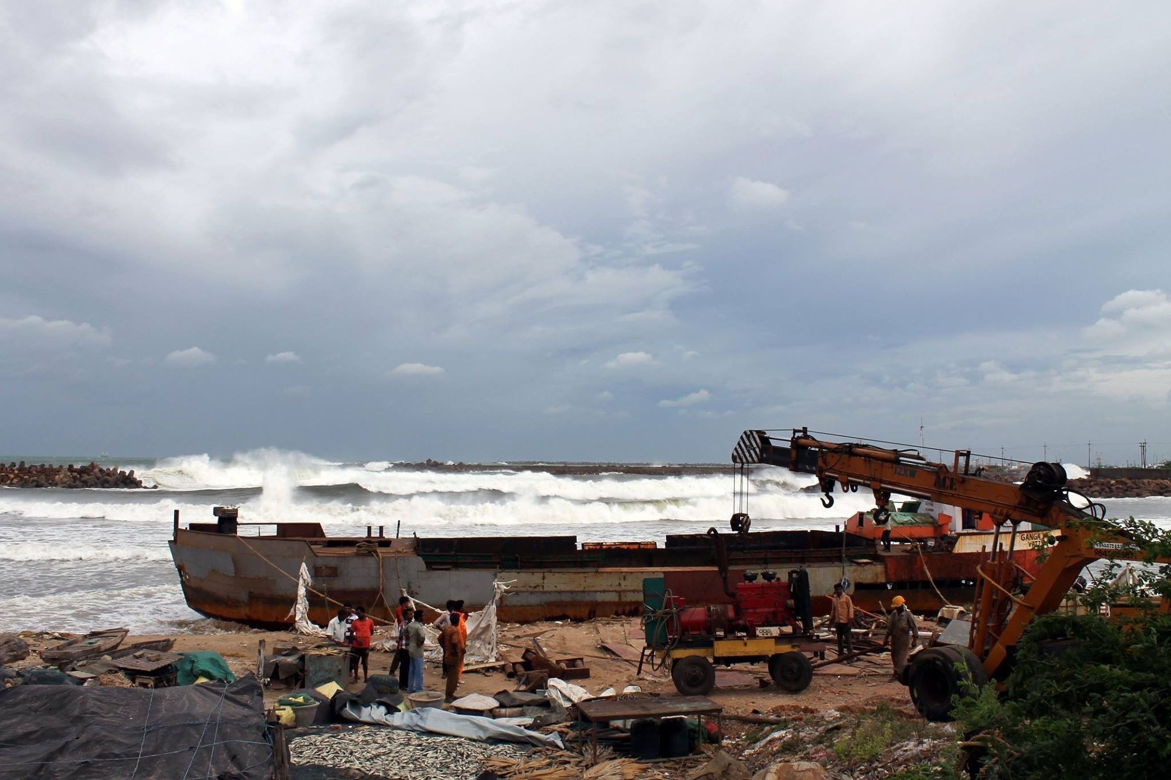 Giant wanted hitting the coast . Cyclone effect . People trying to move their equipment to safer places
